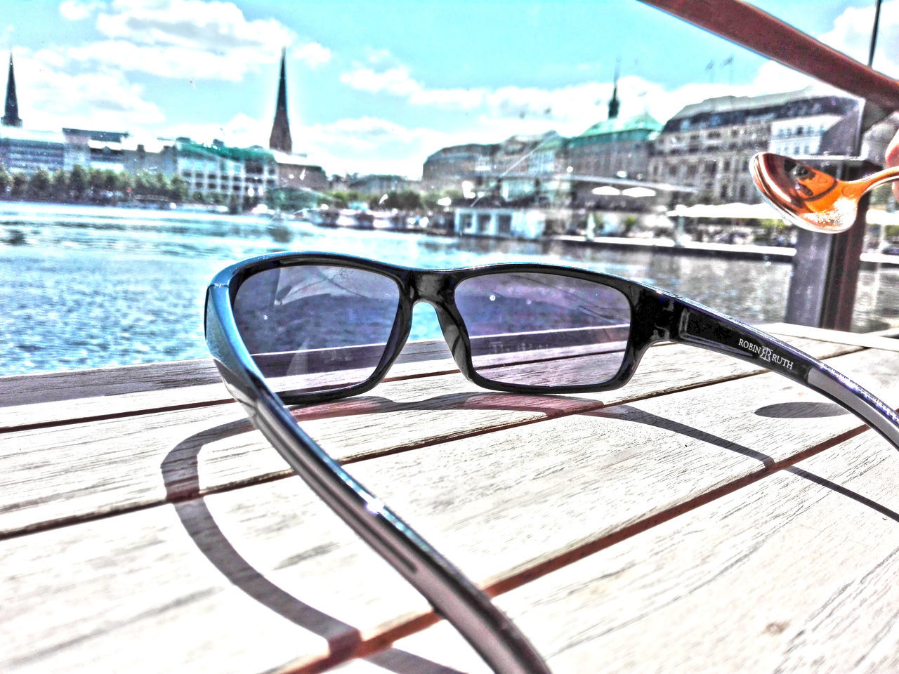 Close-Up Of Sunglasses On Table In City Against Sky