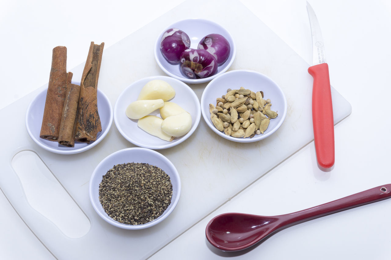 Close-Up Of Spices And Vegetables On Cutting Board Against White Background
