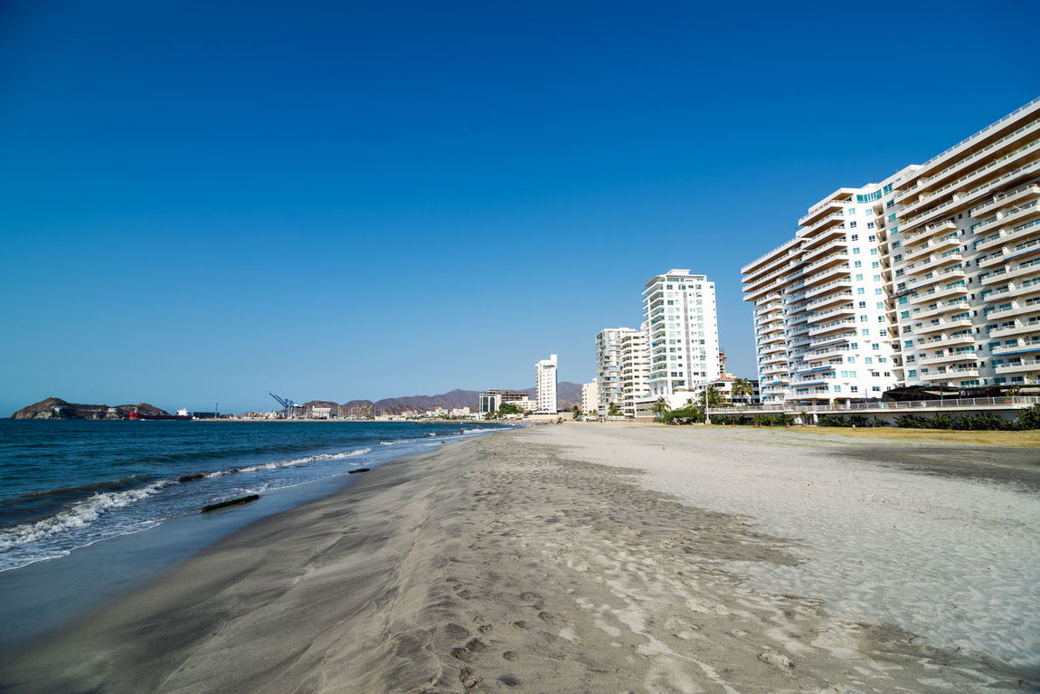 View of beaches on the waterfront of Santa Marta, Colombia America Apartment Architecture Beach Blue Building Caribbean City Coastline Colombia Day Department Landscape Latin Magdalena Outdoors Sand Santamarta Sea Skyline South Vacations View Water White