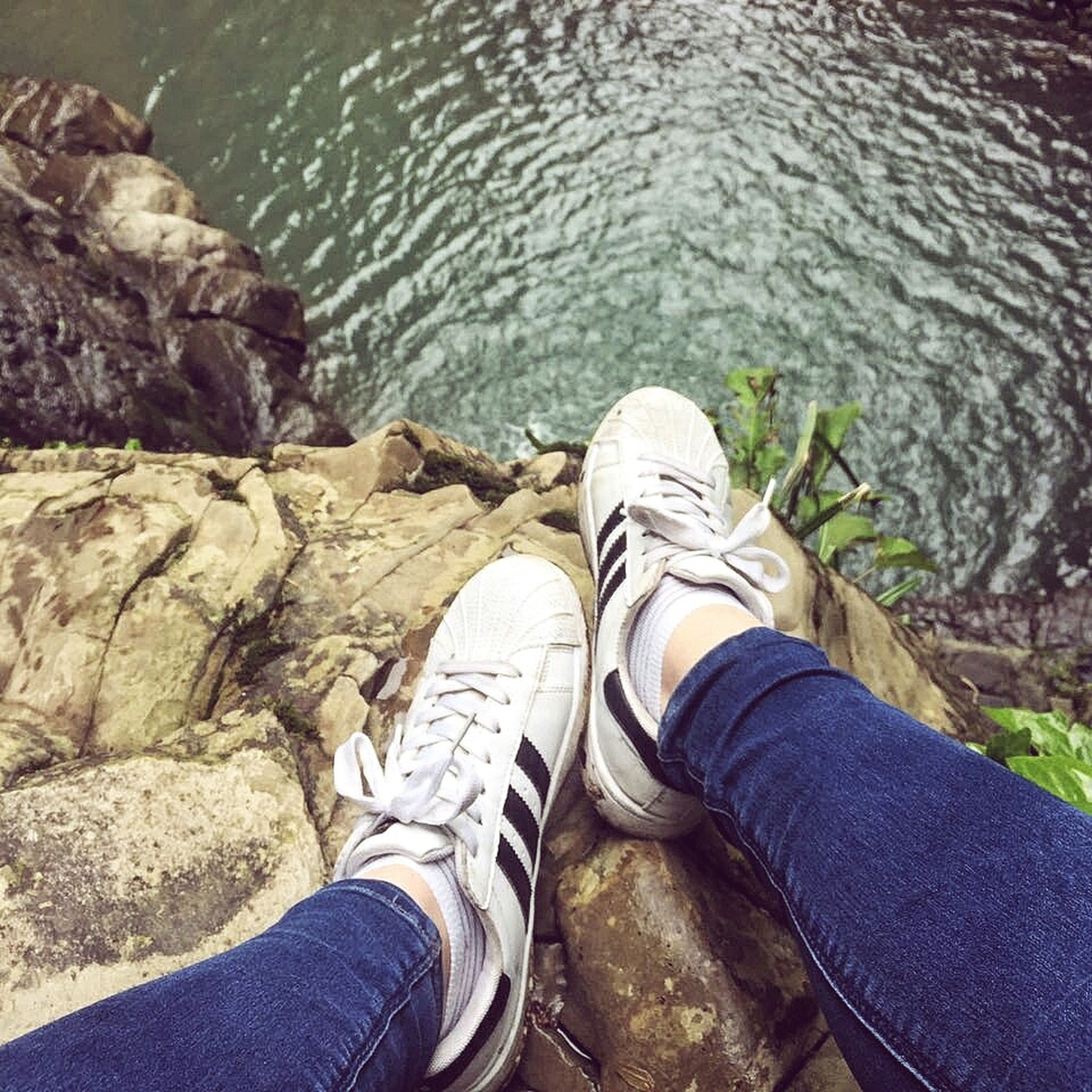 low section, shoe, personal perspective, human leg, water, rock - object, sitting, jeans, real people, high angle view, standing, river, day, outdoors, human body part, lifestyles, riverbank, men, nature, close-up, adult, people