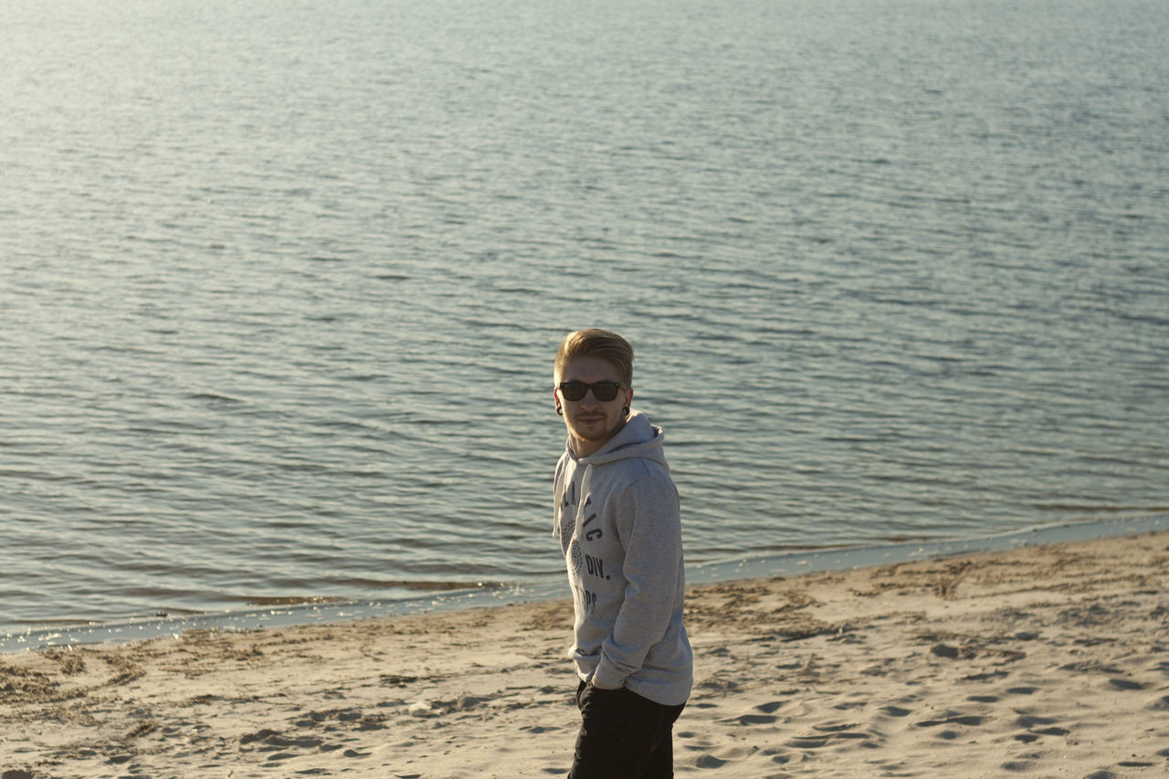 Man In Sunglasses Standing At Beach During Sunny Day