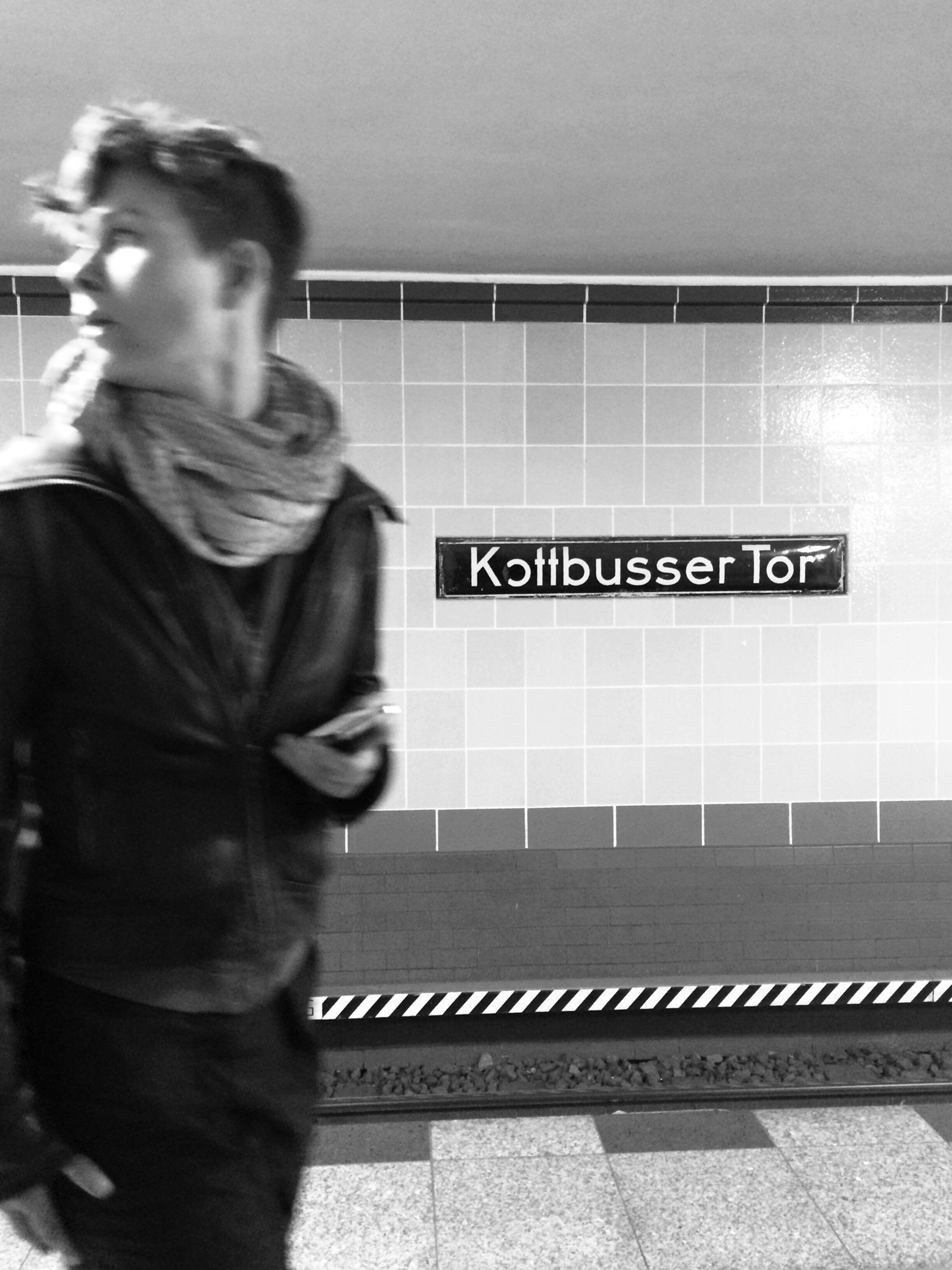communication, text, indoors, lifestyles, western script, railroad station, public transportation, railroad station platform, standing, rail transportation, casual clothing, leisure activity, men, train - vehicle, transportation, technology, three quarter length, subway