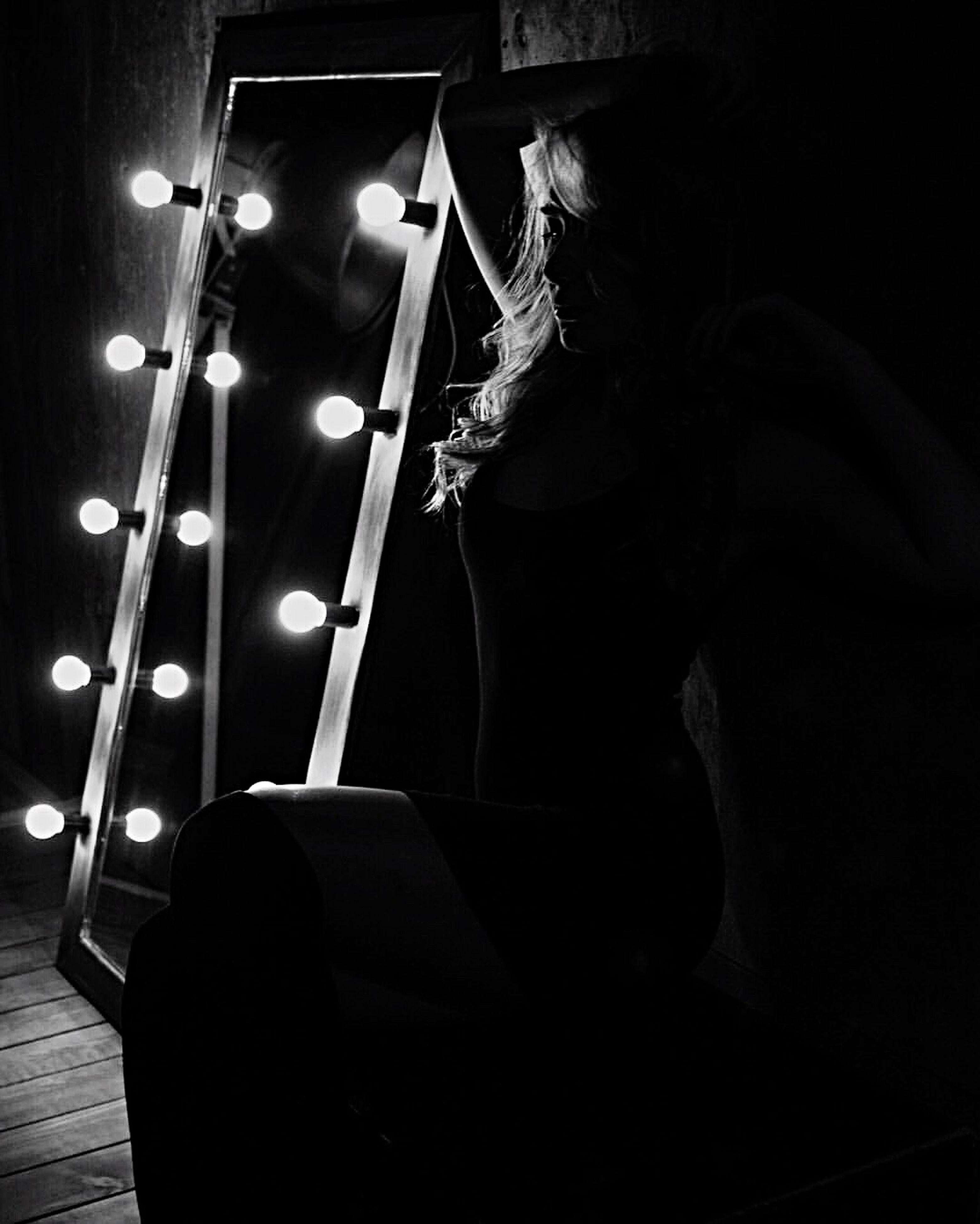 lighting equipment, illuminated, indoors, night, one person, dark, real people, black background, people