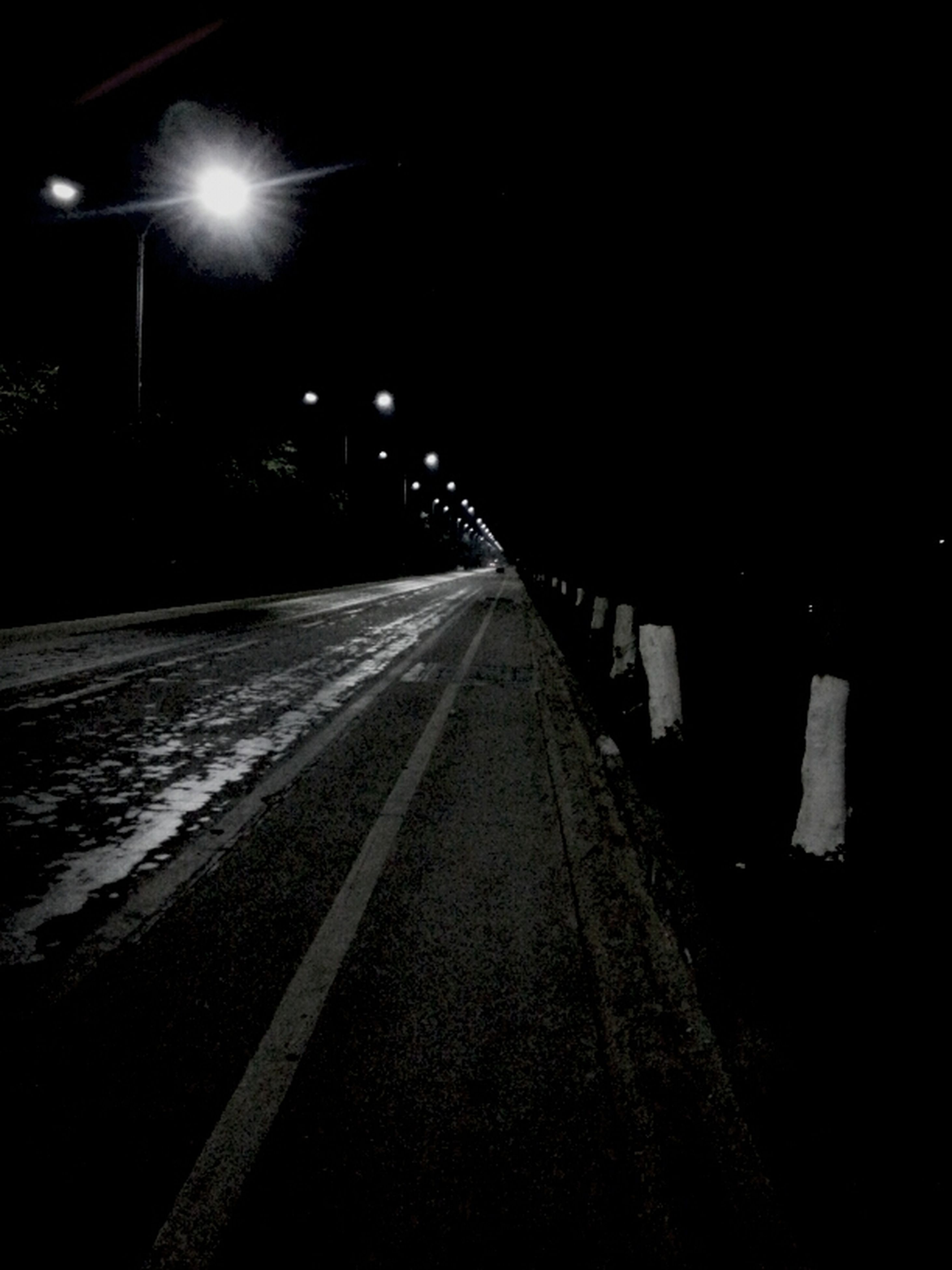night, illuminated, the way forward, transportation, diminishing perspective, street light, road, lighting equipment, vanishing point, street, dark, empty, copy space, long, snow, light - natural phenomenon, road marking, outdoors, winter, no people