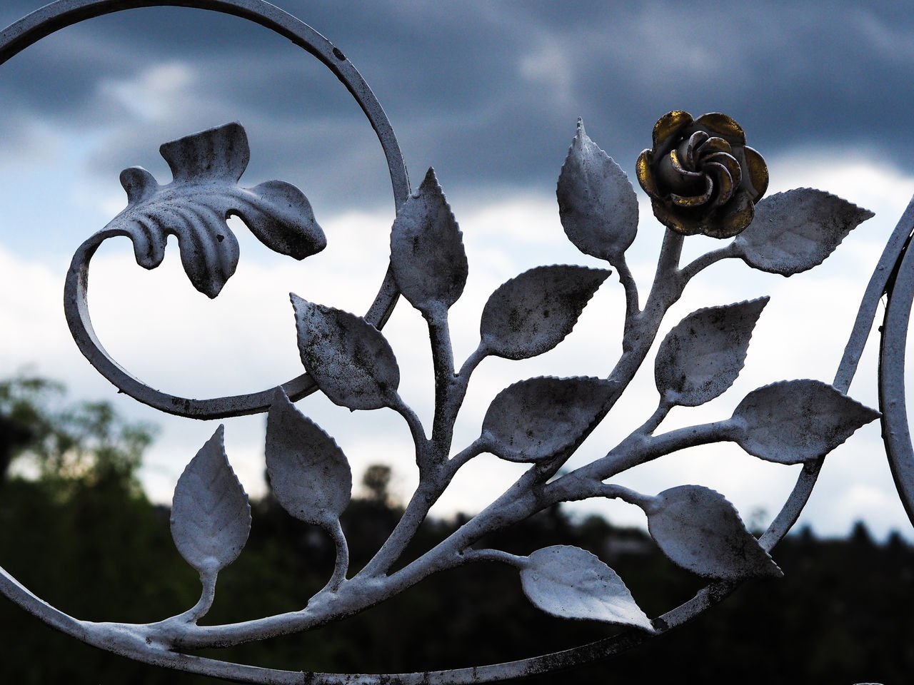 Close-Up Of Leaf And Flower Shape Metal Against Cloudy Sky