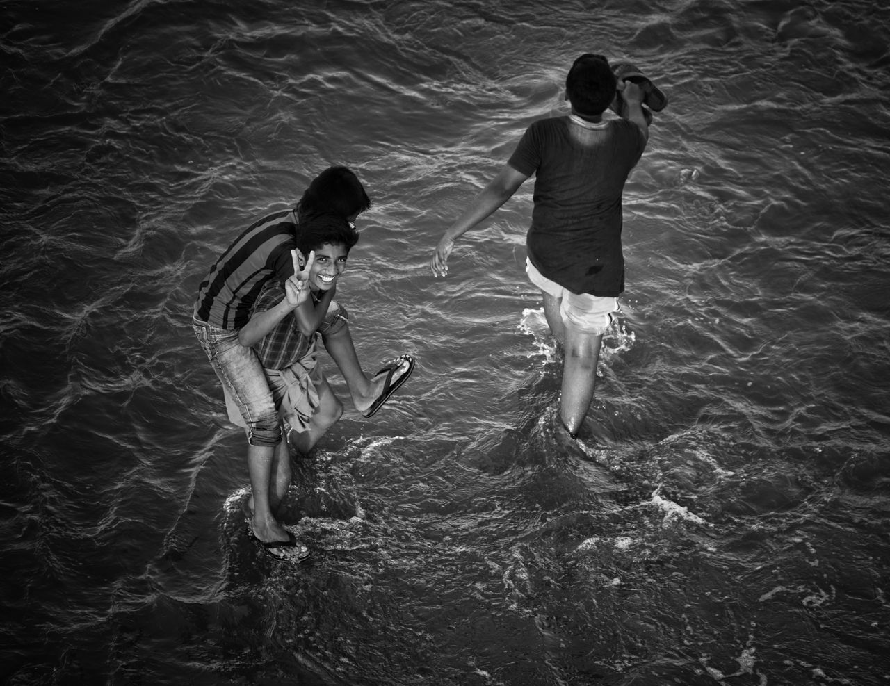 real people, water, high angle view, two people, full length, togetherness, outdoors, day, standing, sea, ankle deep in water, lifestyles, men, nature, swimming, childhood, people
