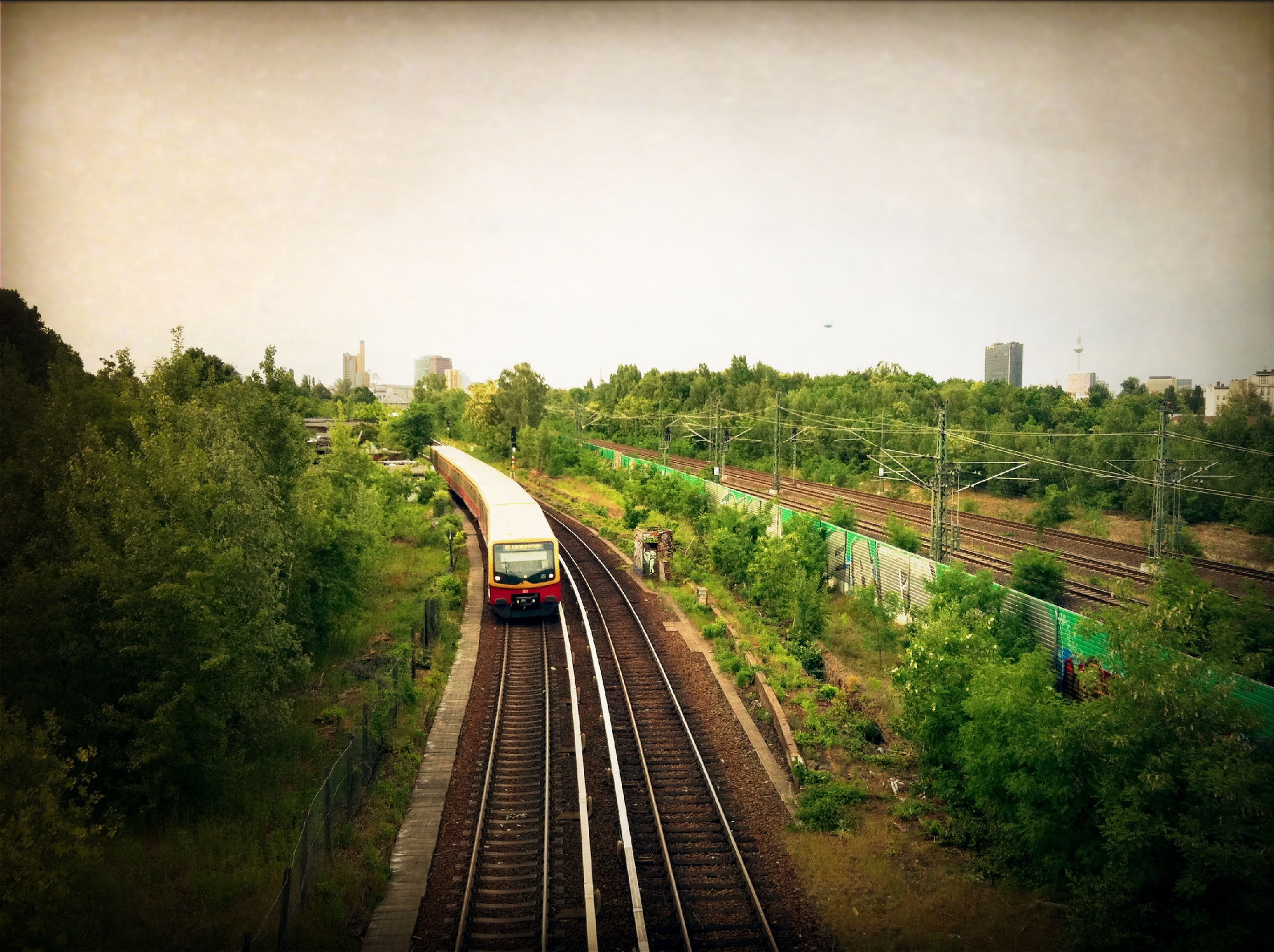 transportation, railroad track, rail transportation, public transportation, mode of transport, train - vehicle, tree, the way forward, clear sky, high angle view, diminishing perspective, on the move, railway track, travel, vanishing point, land vehicle, built structure, train, railroad station, sky
