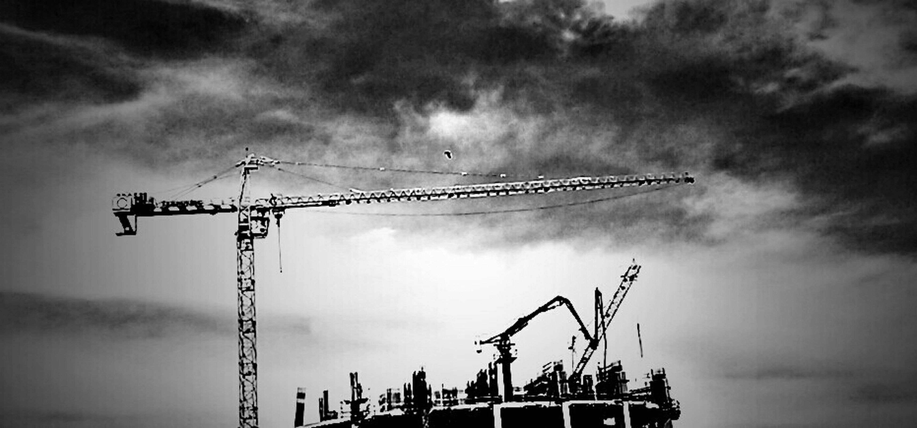 sky, crane - construction machinery, low angle view, cloud - sky, cloudy, construction site, development, crane, fuel and power generation, industry, construction, weather, overcast, cloud, construction industry, alternative energy, wind turbine, environmental conservation, wind power, silhouette