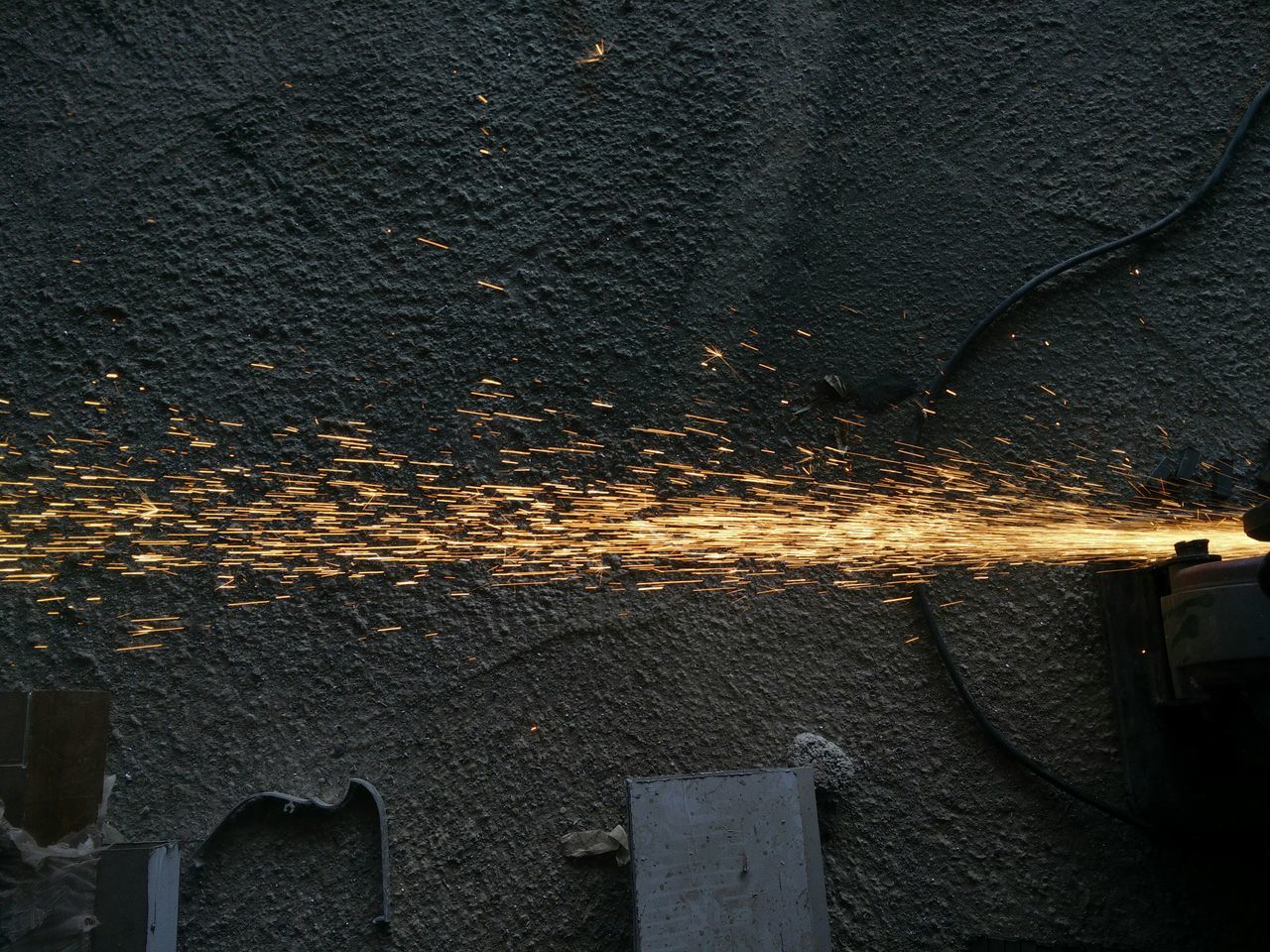 High Angle View Of Sparks Emitting From Grinder In Industry
