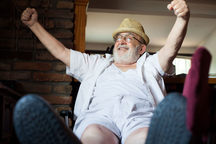 happy old man Arms Raised Background Beard Caucasian Chair Cheerful Comfortable Energetic Fulfillment Good News Happy Indoors  Lifestyles Lively Male Man Old Relaxation Relaxing Resting Retirement Seated Senior Adult Sitting Vitality