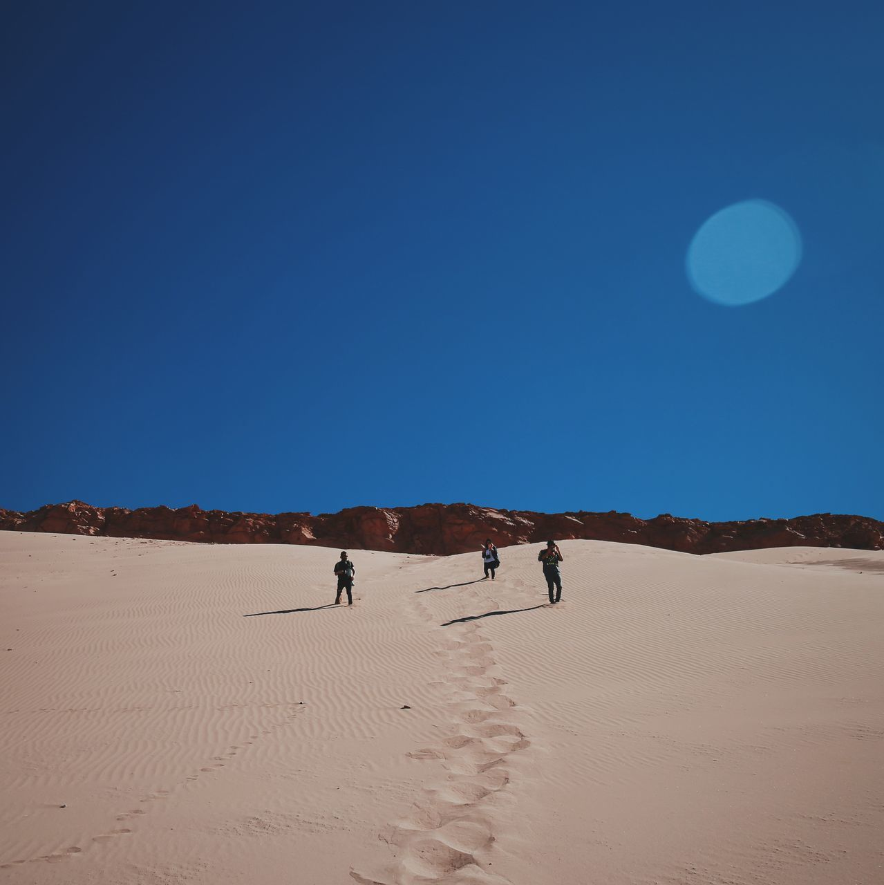 People Standing On Sand With Sky In Background