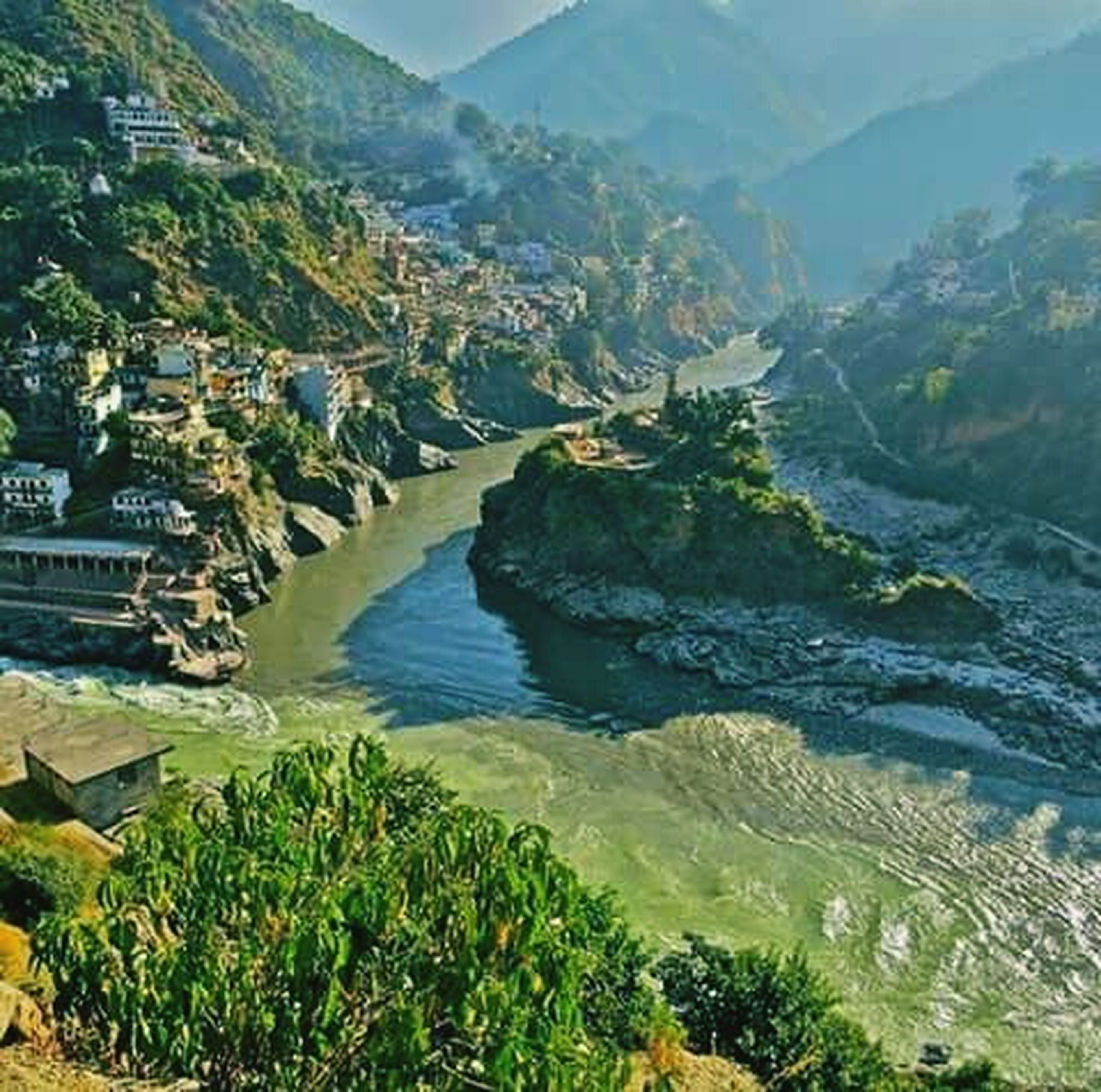 mountain, water, high angle view, building exterior, mountain range, built structure, scenics, architecture, landscape, tree, tranquil scene, river, nature, beauty in nature, tranquility, house, town, sky, residential structure, day