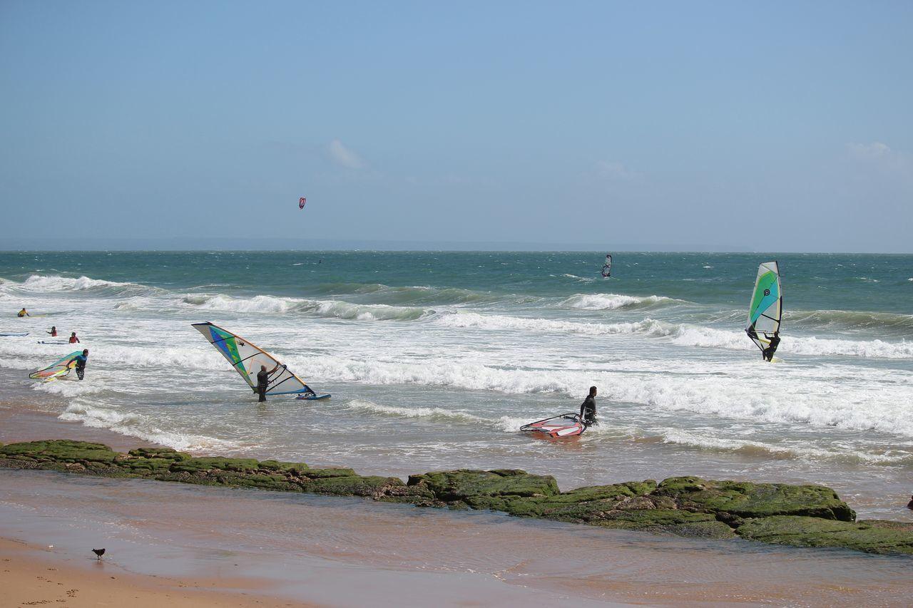 People Windsurfing On Sea Against Sky