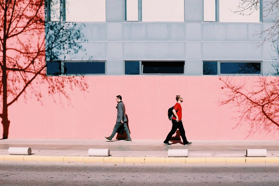 Boys Students Styles Different Casual Clothing Minimalism Outdoors Showcase: February Building Wall Windows Trees Shadows Street Urban Streetphotography Walking Composition People Young Everyday Lives Crossed Lives Street Fashion Two Light And Shadow Millennial Pink