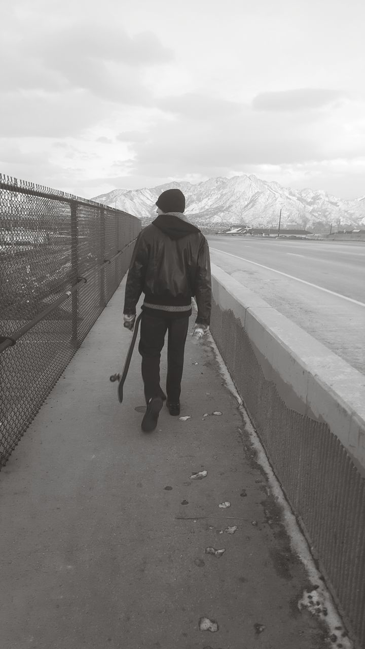 Full Length Rear View Of Man With Skateboard Walking On Sidewalk Against Sky