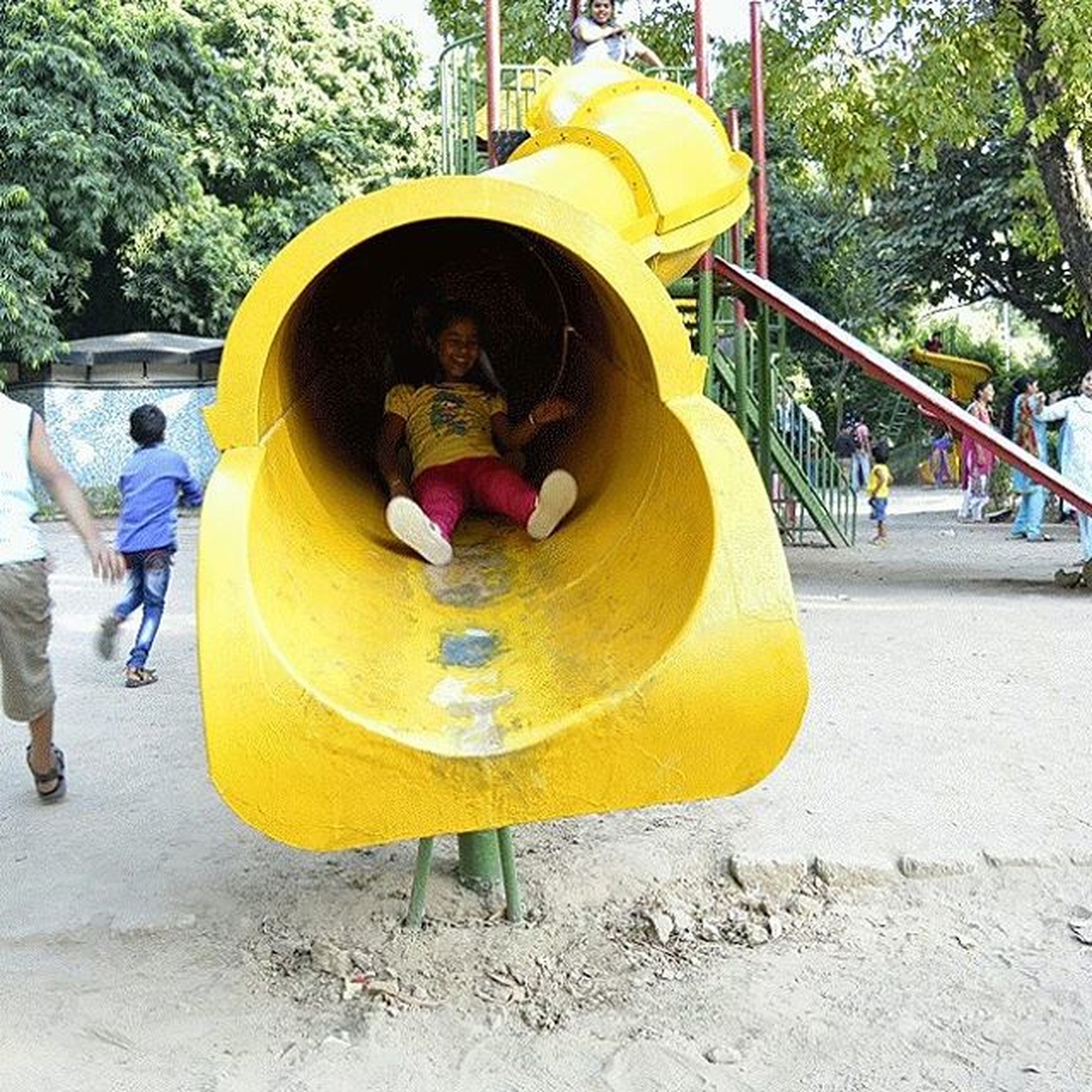 childhood, lifestyles, leisure activity, full length, boys, elementary age, casual clothing, girls, playing, tree, holding, person, playground, innocence, fun, park - man made space, playful, yellow