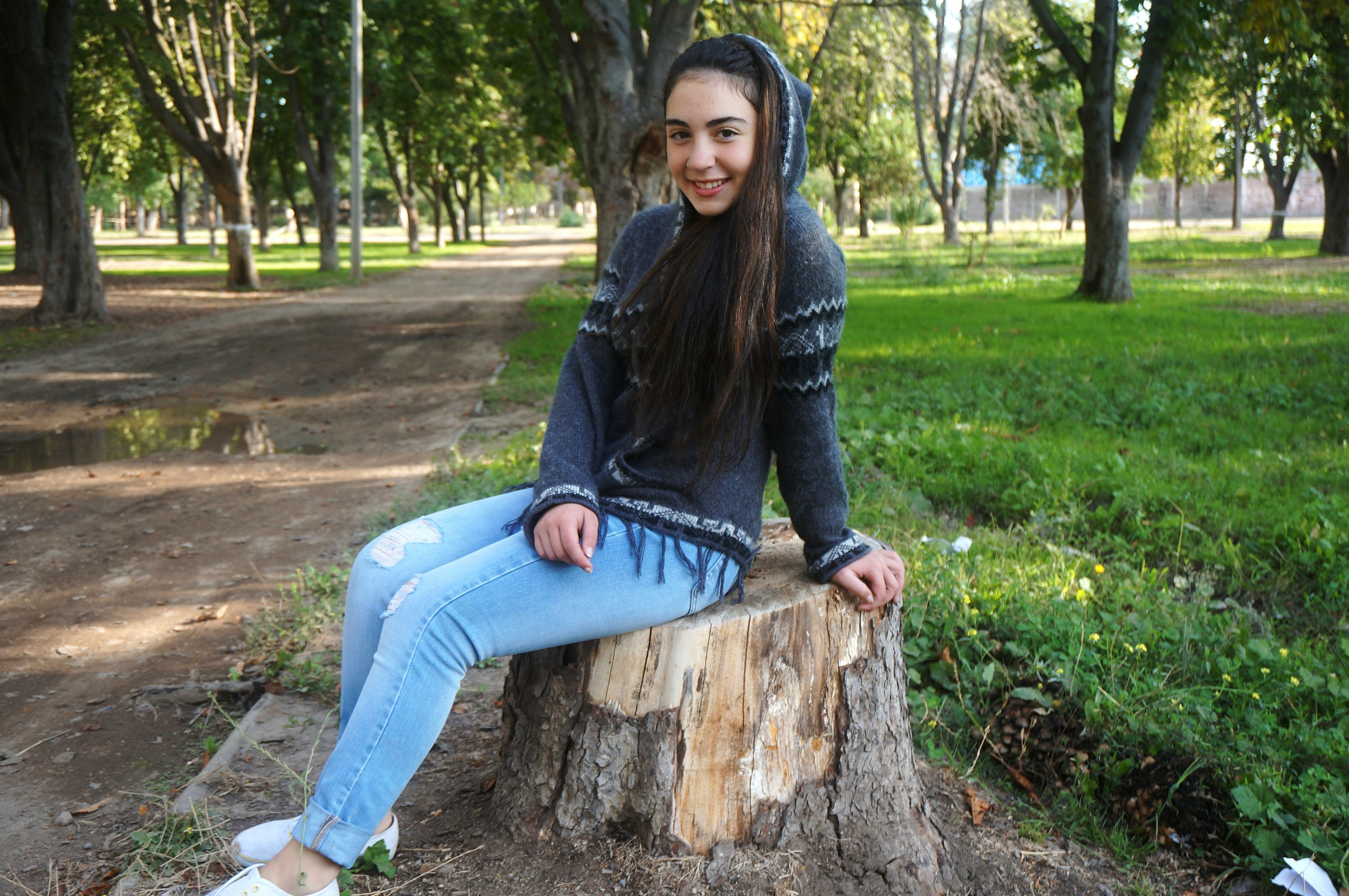 young adult, person, looking at camera, portrait, front view, casual clothing, tree, lifestyles, young women, leisure activity, smiling, standing, long hair, happiness, confidence, full length, three quarter length
