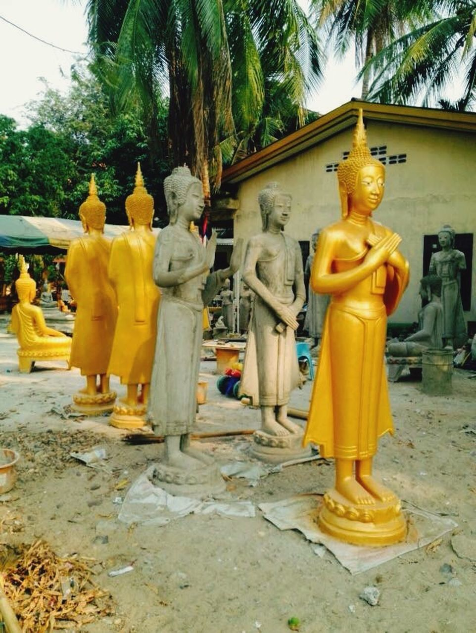 male likeness, statue, human representation, religion, sculpture, spirituality, yellow, art and craft, tree, idol, golden color, no people, day, outdoors