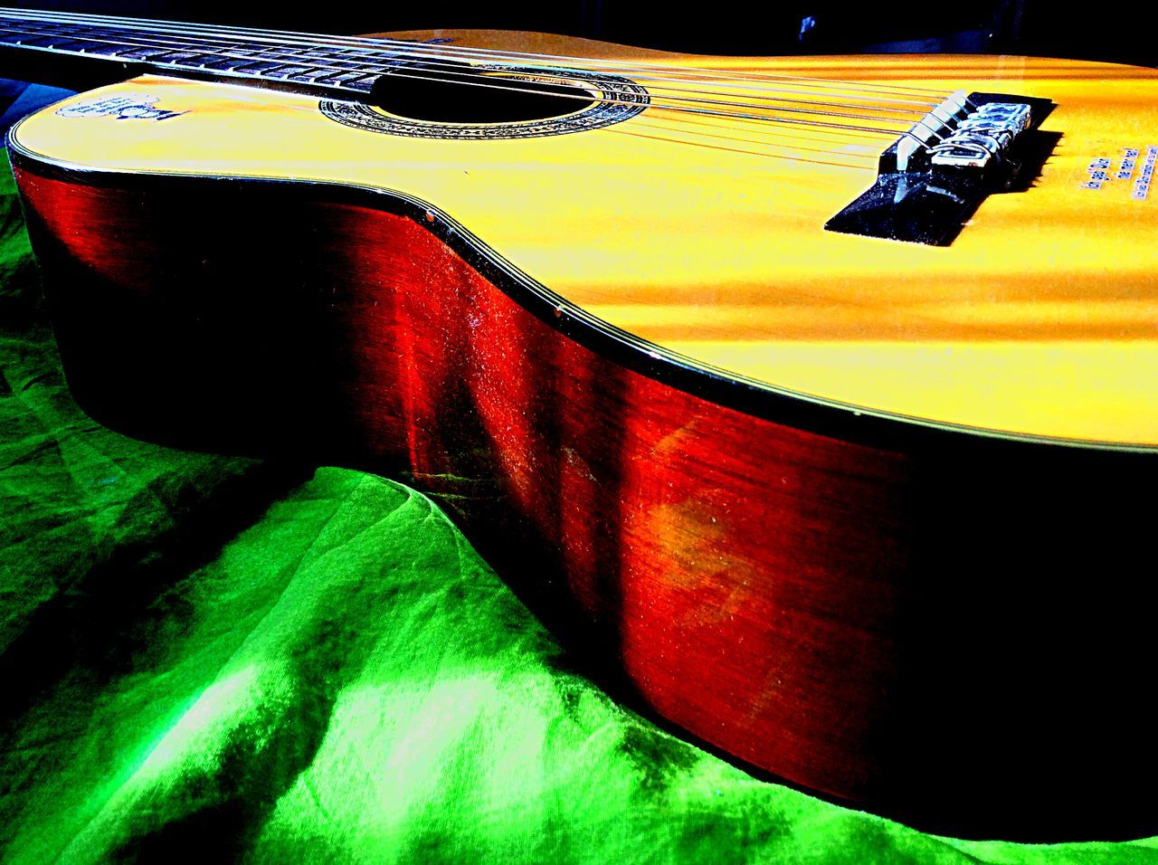 Close-Up Of Acoustic Guitar On Green Fabric