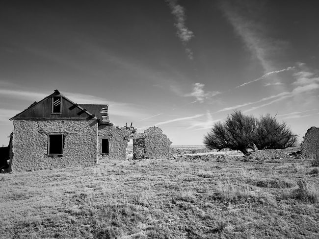 """""""Mystery Ranch"""" For over four years I have driven past this abandoned ranch house set back off Highway 42 in New Mexico, always wanting to photograph it. My hesitation was a gated fence onto the private ranch land. Finally on January 2, 2018 I parked my truck at the gate, climbed over it and walked the near mile into the property and shot my long desired series of the ranch dwellings and surrounding area. It's a mysterious set of buildings and inspecting it only made my curiosity grow even more wondering what the story and history behind it was. Thus I've titled the series """"Mystery Ranch."""" It includes both black and white interpretation as well as color as the subject demanded both in its varied study. New Mexico Photography New Mexico Abandoned Places Abandoned Buildings Ranch Black And White Photography Black And White Architecture Building Exterior Built Structure Sky No People Field Landscape"""