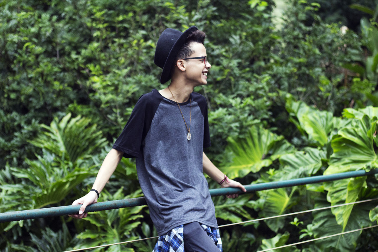 Beauty In Nature Black Hair Carefree Casual Clothing Day Eyeglasses  Freedom Green Green Color Happiness Nature One Person Outdoors People Real People Responsibility Teenager Tree Young Adult