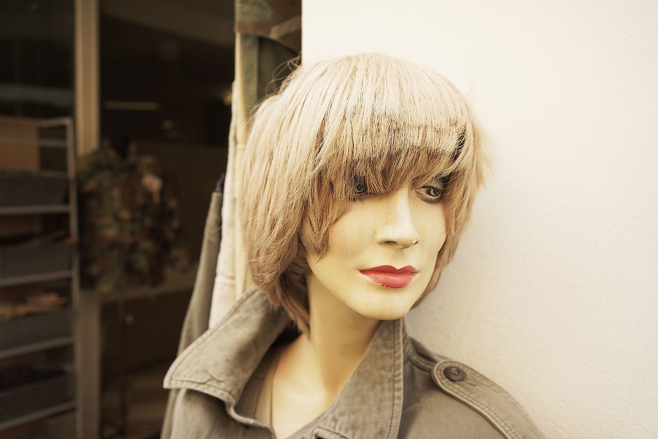 Close-Up Of Female Mannequin With Wig Against Wall