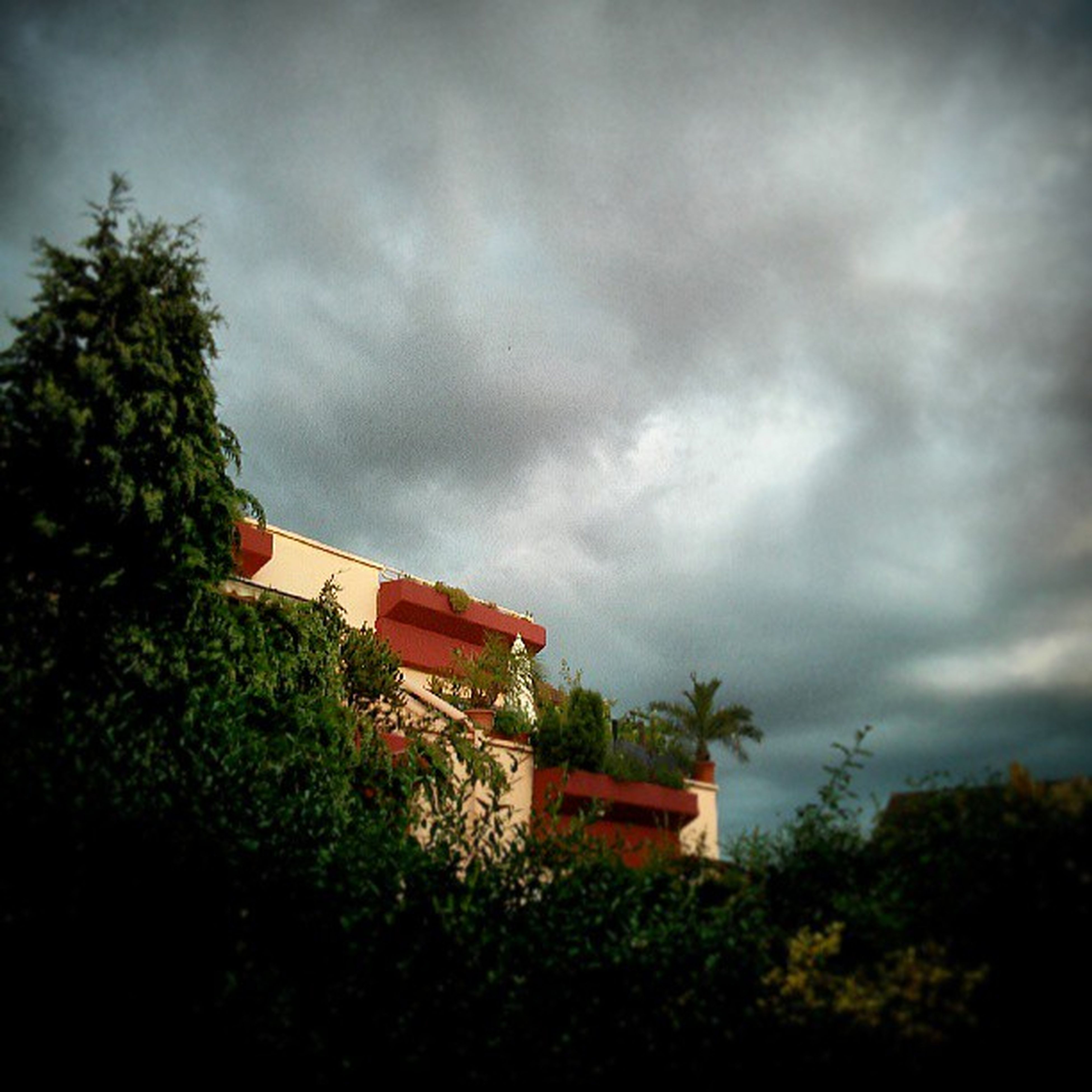 sky, building exterior, cloud - sky, cloudy, architecture, built structure, tree, weather, house, overcast, storm cloud, cloud, growth, nature, residential structure, green color, residential building, plant, low angle view, outdoors