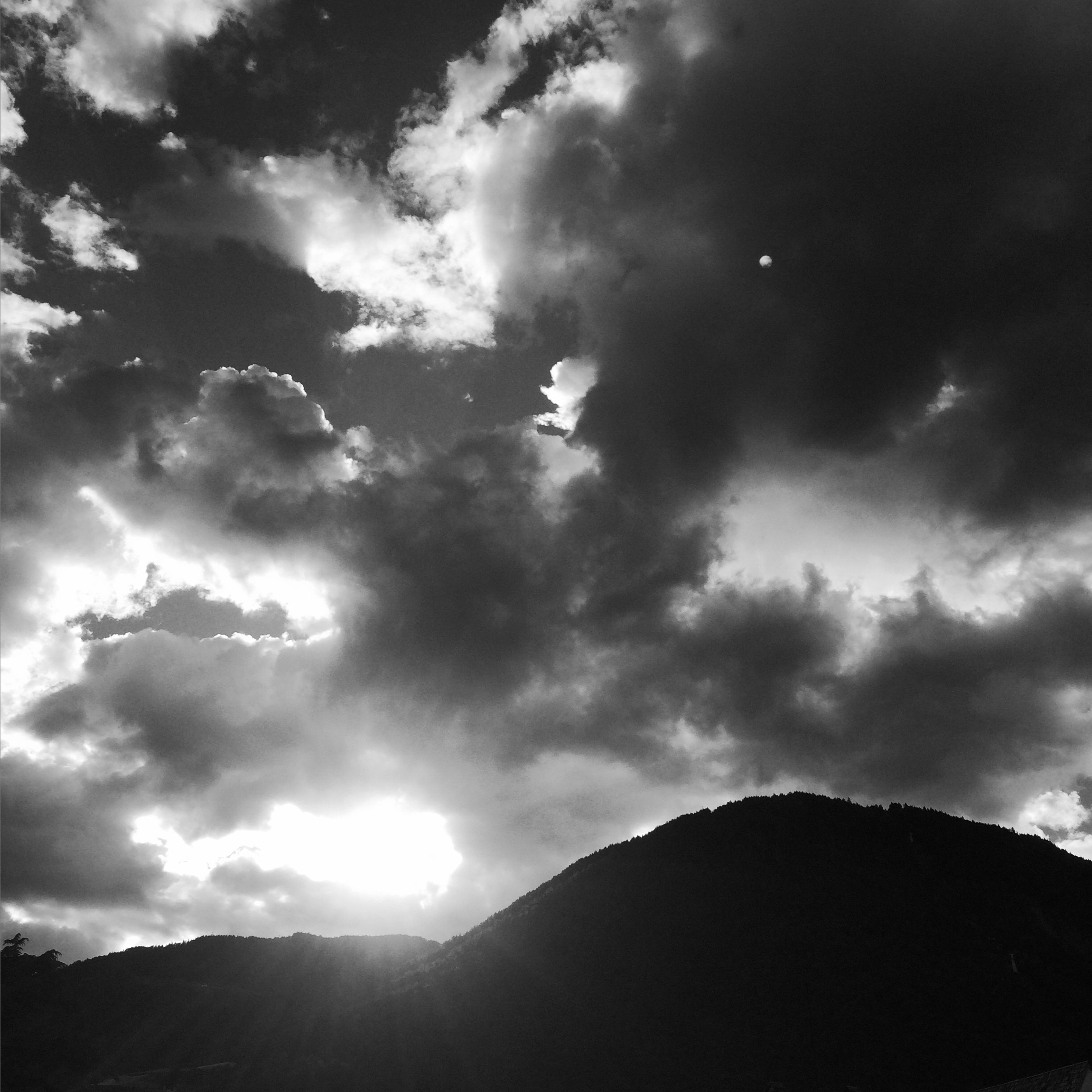 sky, cloud - sky, low angle view, flying, sun, sunbeam, beauty in nature, cloudy, bird, nature, cloud, sunlight, silhouette, scenics, animal themes, tranquility, tranquil scene, mountain, mid-air, day