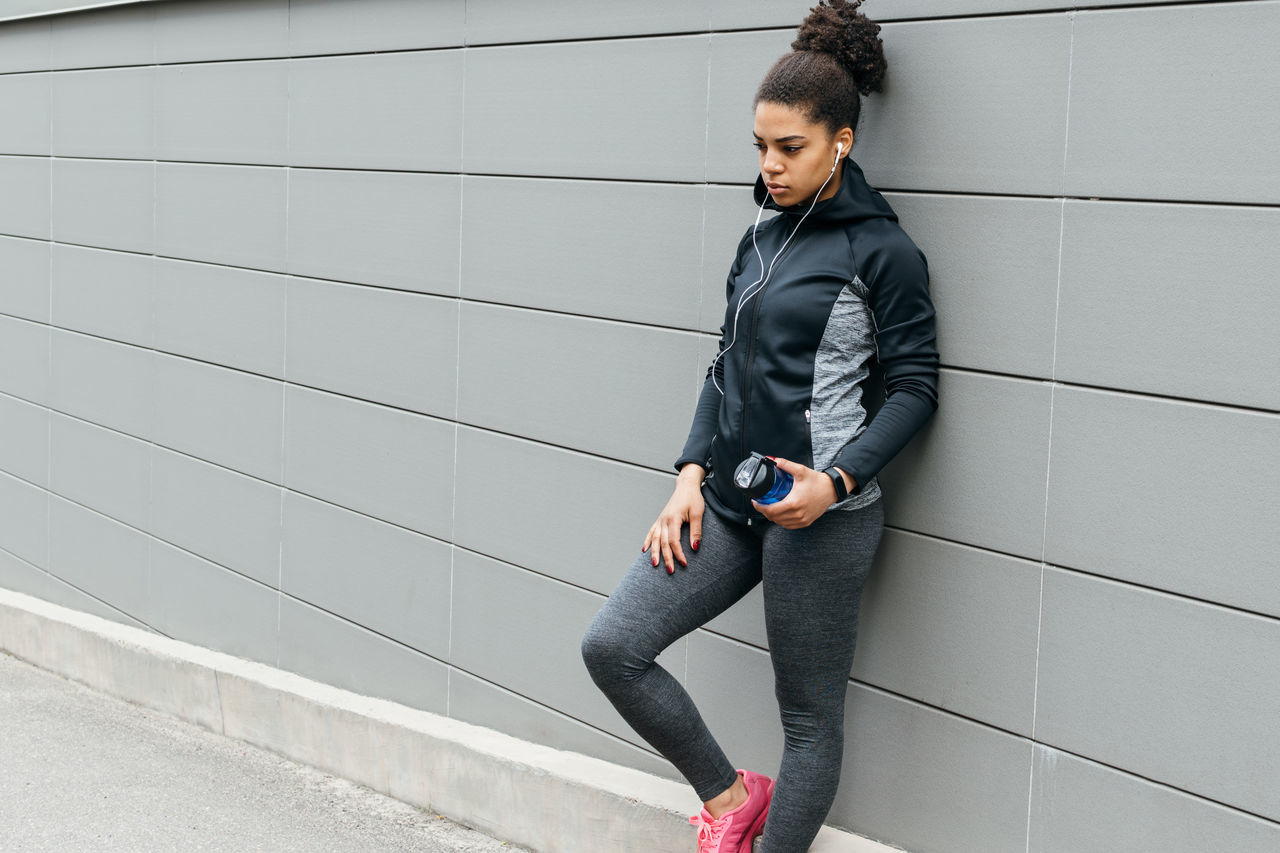 African American Beautiful Woman Black Hair Day Fitness Headphones Healthy Lifestyle Leaning Leisure Activity Looking Down One Person One Woman Only One Young Woman Only Portable Information Device Sport Sport Clothes Standing Street Technology Training Wall Wireless Technology Young Adult