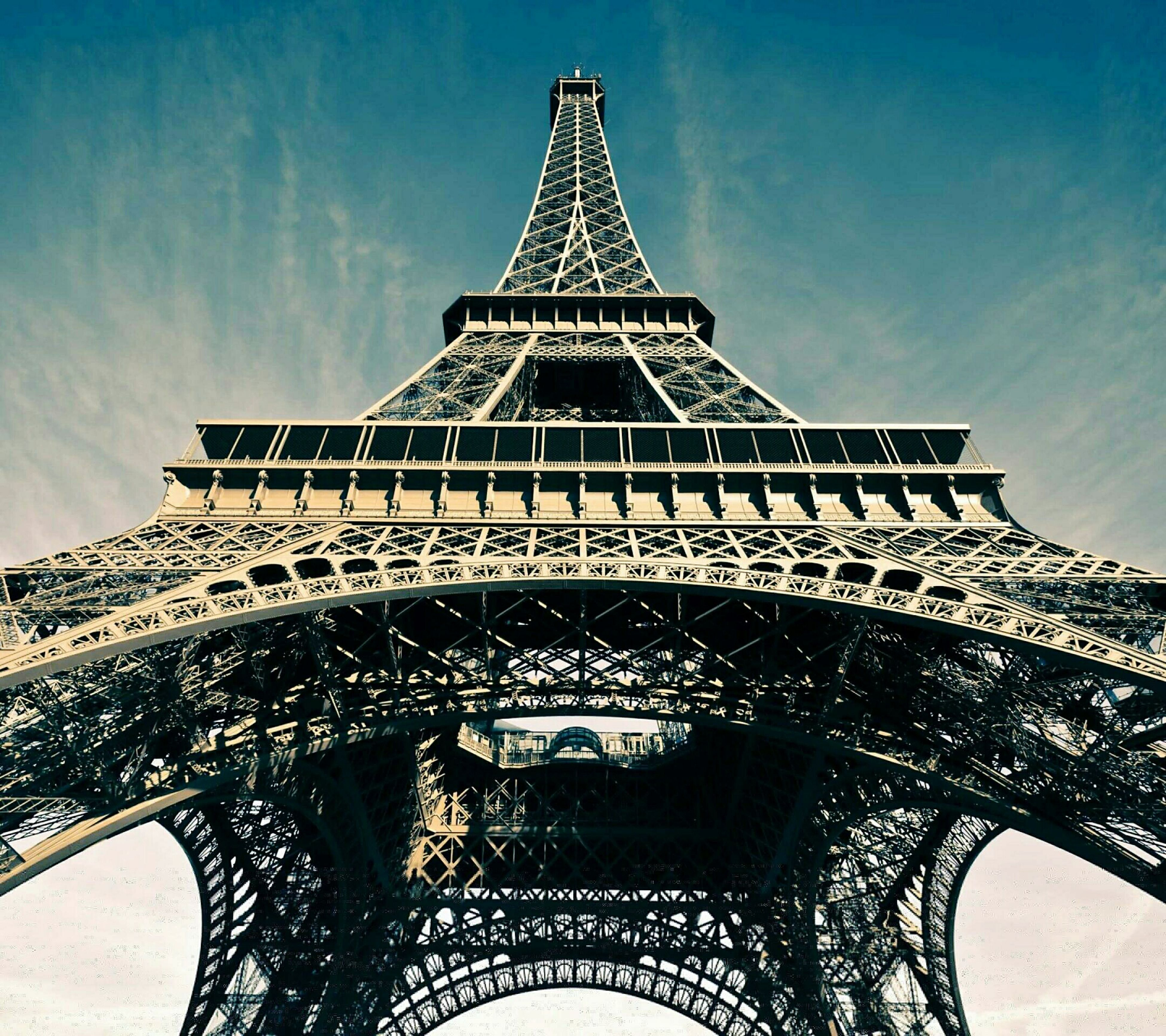 architecture, famous place, built structure, international landmark, low angle view, eiffel tower, travel destinations, tourism, culture, capital cities, travel, tower, architectural feature, history, sky, metal, tall - high, building exterior, day, city