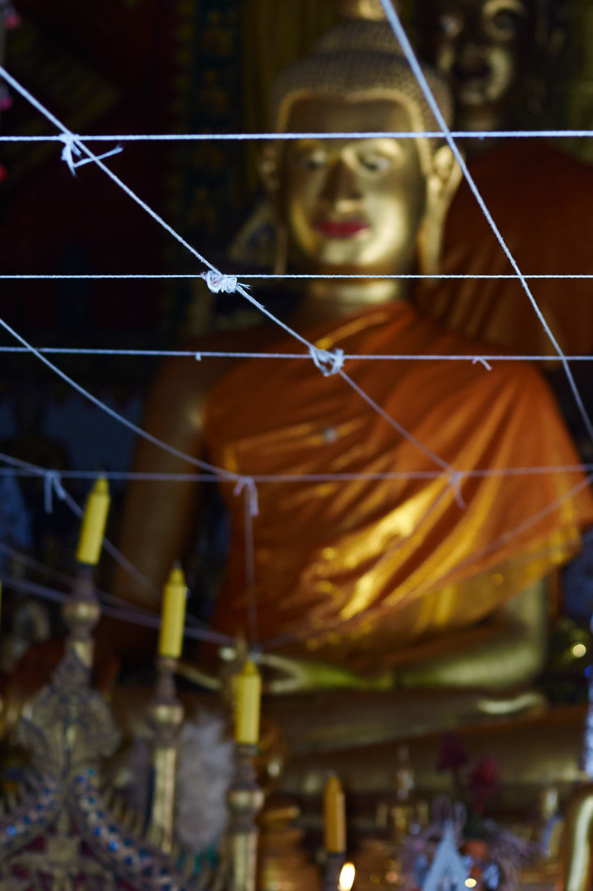 Low Angle View Of Decoration Against Buddha Statue At Temple
