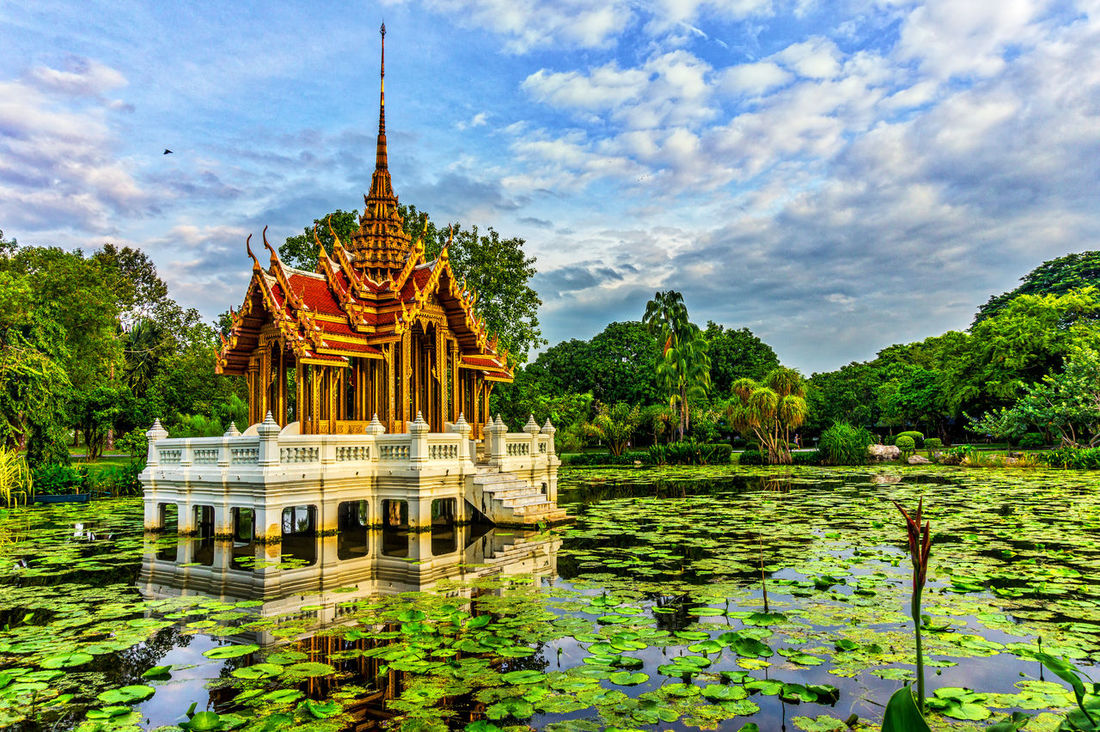 Temple on a lake surrounded by water lilies. Architectural Feature Architecture Building Exterior Built Structure Cloud Cloud - Sky Day Gazebo Green Color Growth Nature Pagoda Place Of Worship Plant Pond Reflection Scenics Sky Spire  Temple - Building Tranquil Scene Tranquility Tree Water Waterfront