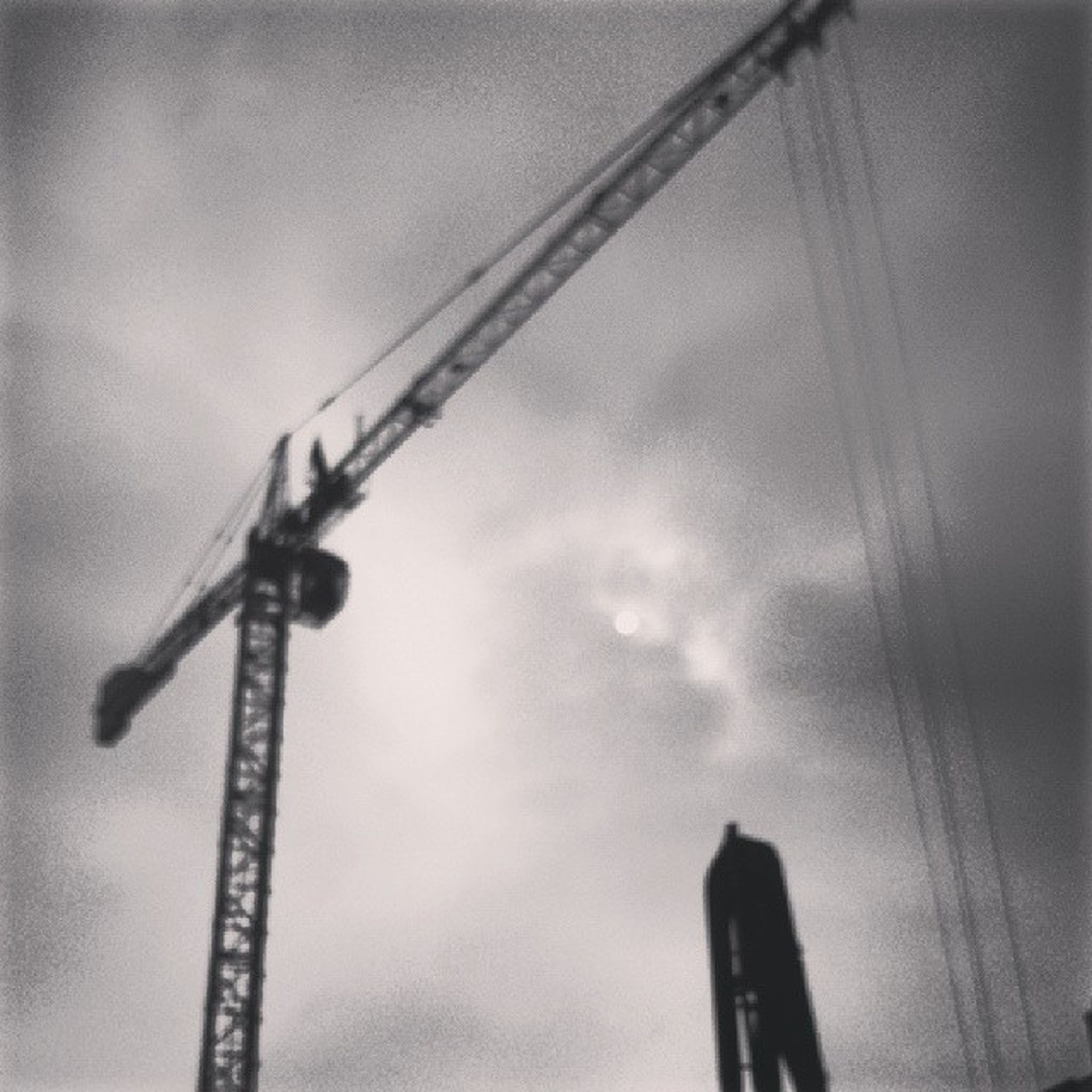low angle view, sky, metal, crane - construction machinery, electricity, industry, development, construction site, technology, metallic, no people, cloud - sky, connection, outdoors, fuel and power generation, dusk, silhouette, construction, power supply, day