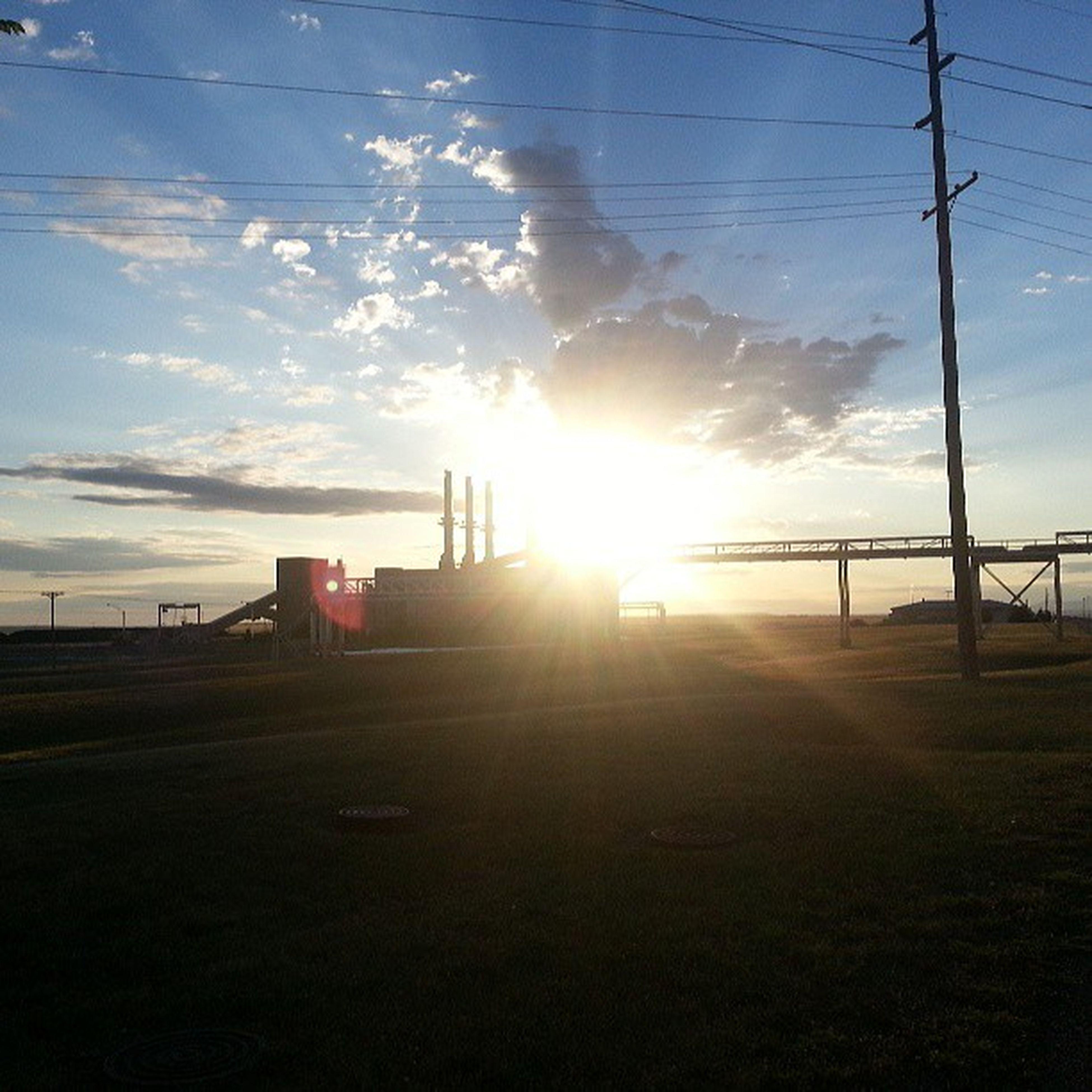 sun, sky, sunset, sunbeam, sunlight, cloud - sky, built structure, architecture, lens flare, silhouette, building exterior, cloud, electricity pylon, power line, nature, cloudy, tranquility, outdoors, tranquil scene, scenics