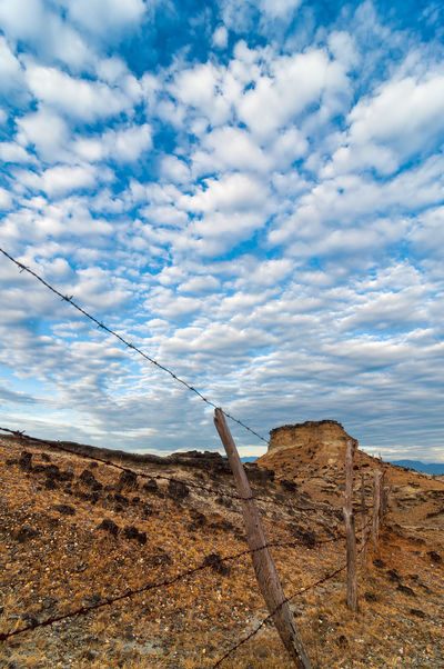 Old worn out fence in a desolate desert under a dramatic blue sky Arid Beautiful Clouds Colombia Desert Desolate Drought Dry Environment Heat Hot Huila  Landscape Nature Nature Outdoors Scenery Scenic Southernmost Stone Tatacoa Three Travel View Wilderness