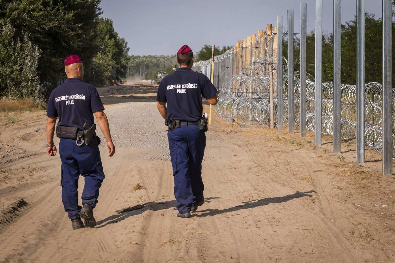 Firewall against illegal immigrants and refugees on the border between Hungary and Serbia Barbed Wire Barbed Wire Fence Border Borderline Fence Firewall Frontier Frontière Guards Patrol  Patroling Policeman At Work Policeman Patrol Point Real People Rear View State Border Togetherness