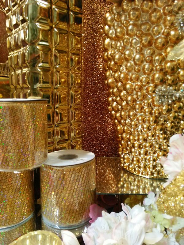 At the Shinoda Design Center, a vast Wholesale Market for the Interiordecorator . Silk Flowers and Artificial Plants Tchotchkies Wedding Decor Holiday Decor Home Decor Home Decoration  Interior Decorating Decorations Restaurant Decor Christmas Decorations Halloween Decorations Halloween Decor you name it. The place goes on forever in a giant Warehouse and is Overwhelming on your first visit. The endcaps of every aisle feature a lavishly overdone display staying within a theme or color scheme ...this picture is a close-up of a setting for Christmas focusing on just metallic gold. Everything in the display is available in the adjacent aisle if not directly under the display. Metallic Gold Golden Pottery Vases Ribbons Sequins Textures And Surfaces