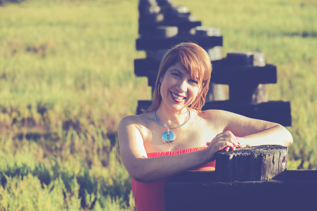 Pretty woman posing outdoors for a portrait, grass and wooden structure in the background Casual Clothing Enjoyment Focus On Foreground Freshness Front View Headshot Hispanic Holding Latina Leisure Activity Lifestyles Person Pretty Girl Pretty Woman Relaxation Woman 40s Woman Portrait Woman Portraiture Woman Smiling