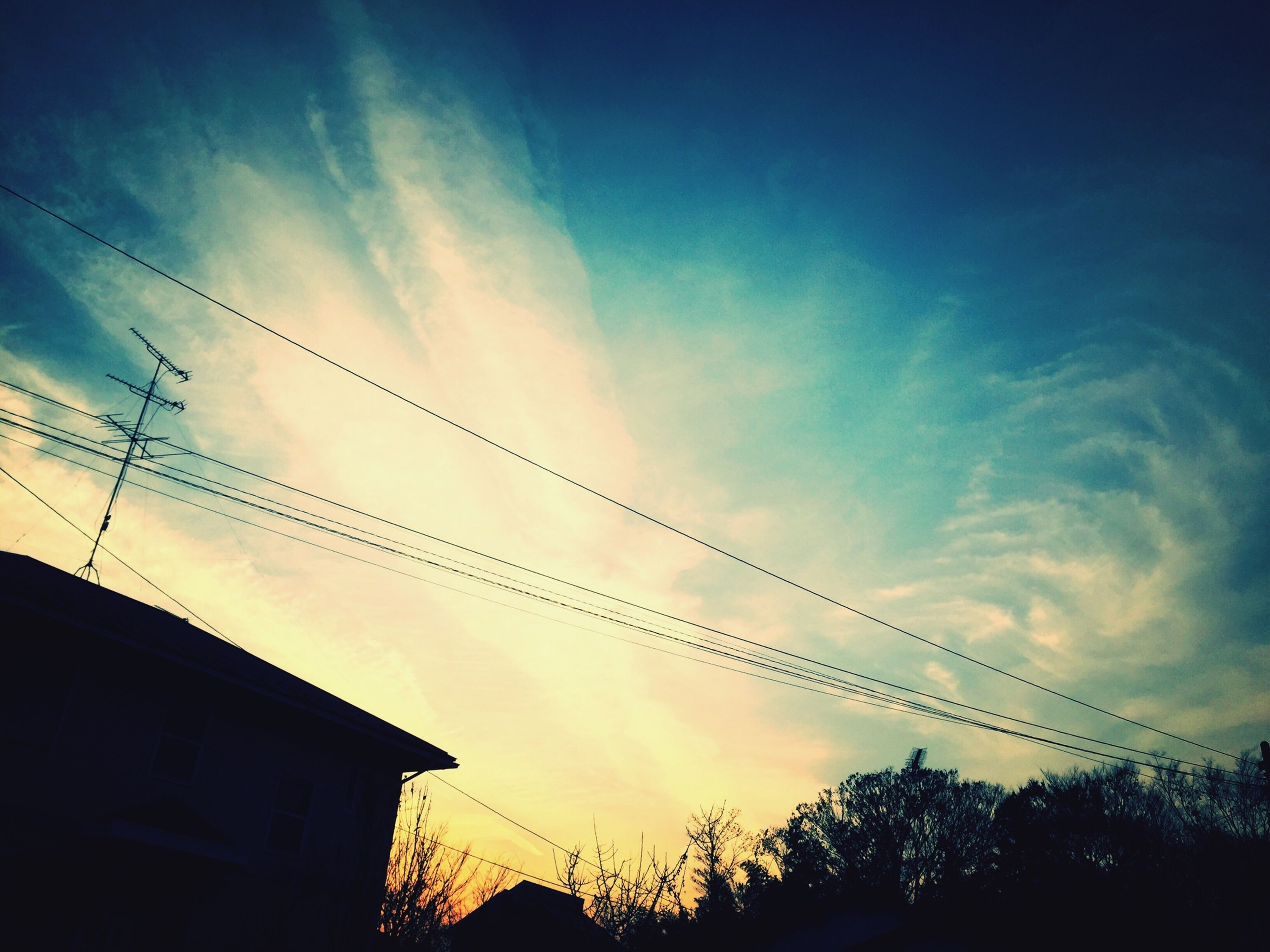 low angle view, silhouette, sky, building exterior, built structure, architecture, sunset, cloud - sky, house, power line, cloud, blue, nature, outdoors, high section, no people, beauty in nature, residential structure, dusk, building