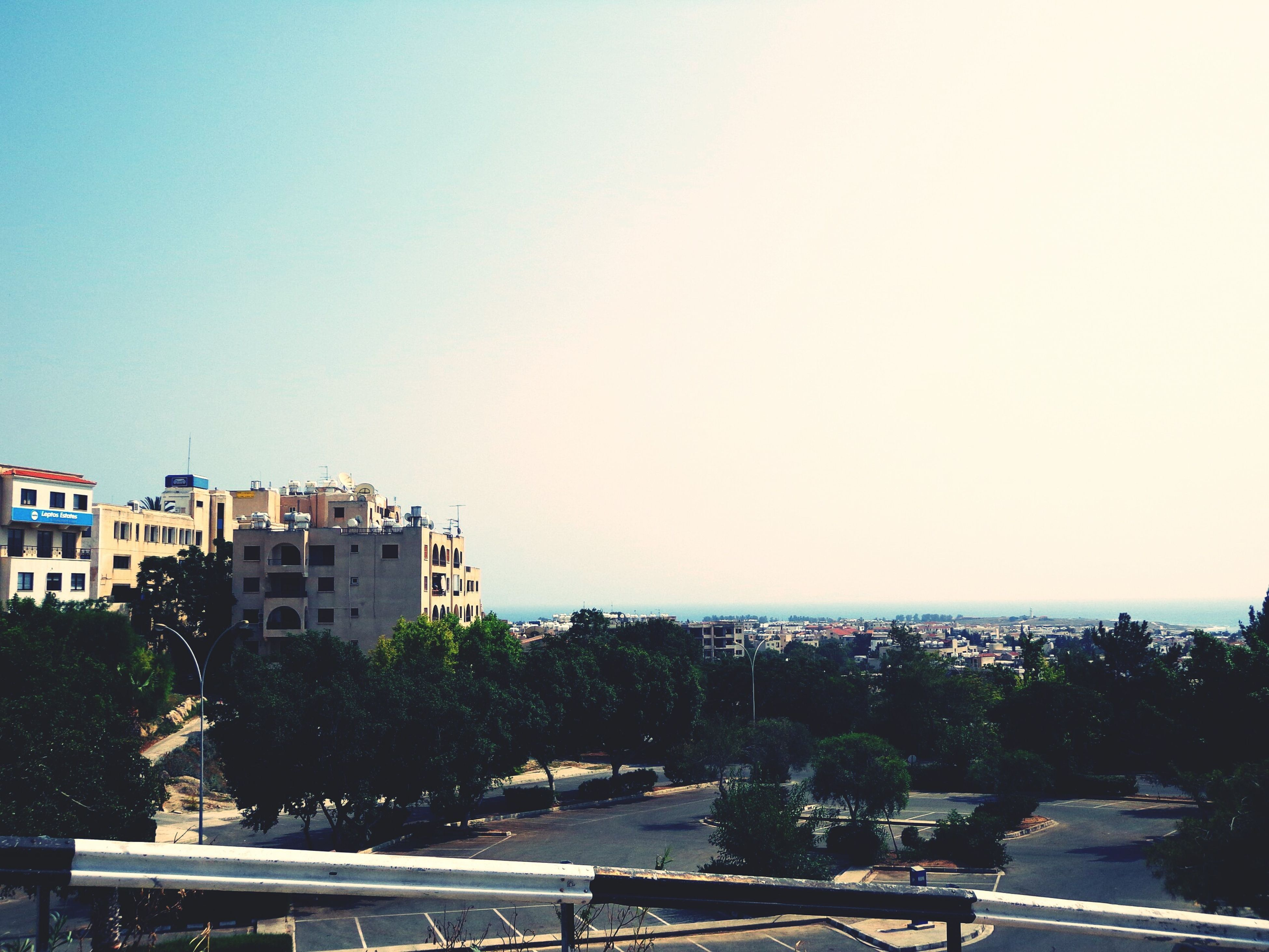 building exterior, clear sky, architecture, built structure, copy space, city, cityscape, residential district, residential structure, tree, residential building, high angle view, house, street, road, car, crowded, city life, day, outdoors