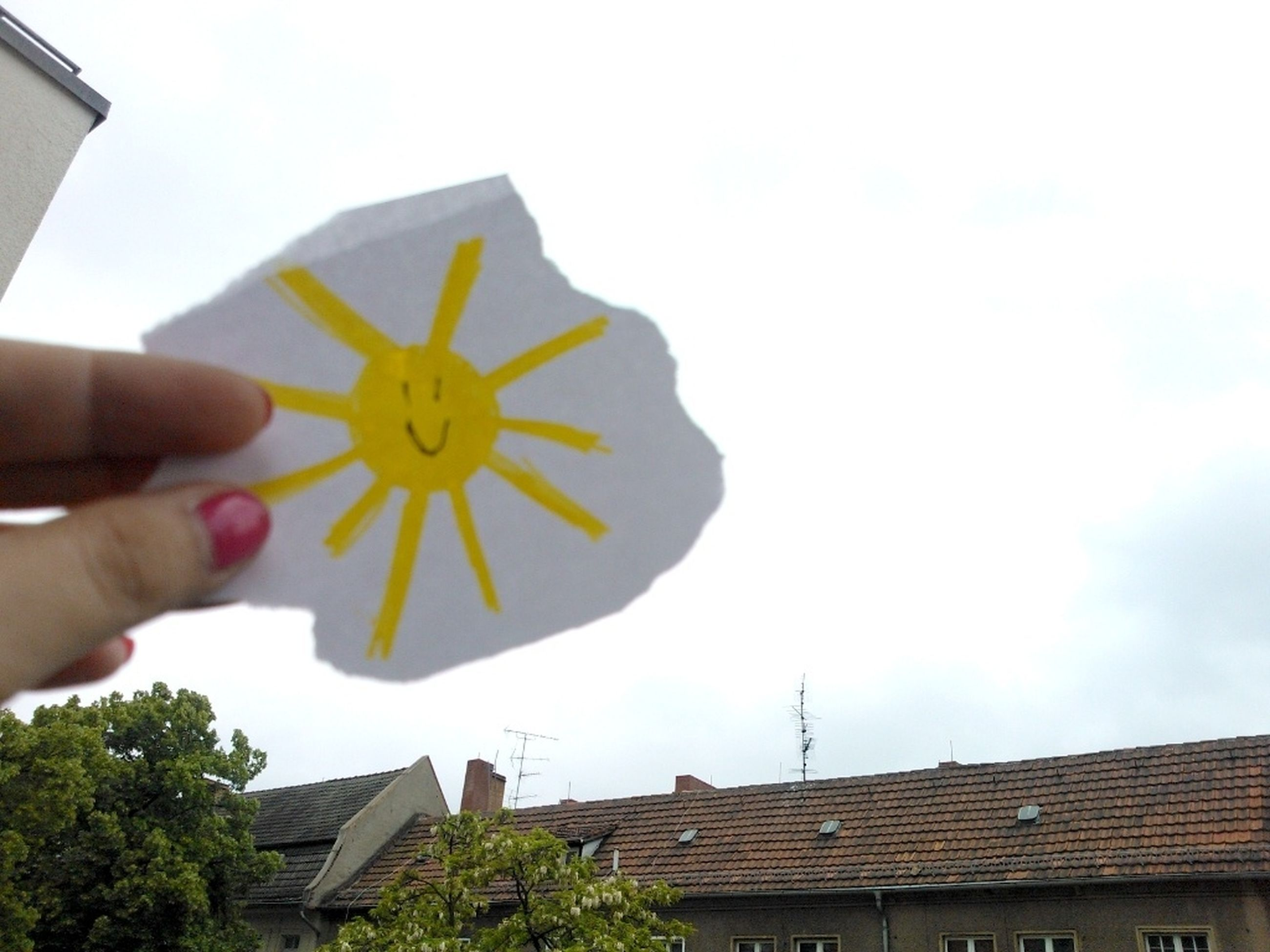 person, building exterior, architecture, built structure, cropped, holding, part of, sky, house, low angle view, roof, yellow, human finger, day, outdoors, unrecognizable person, flower
