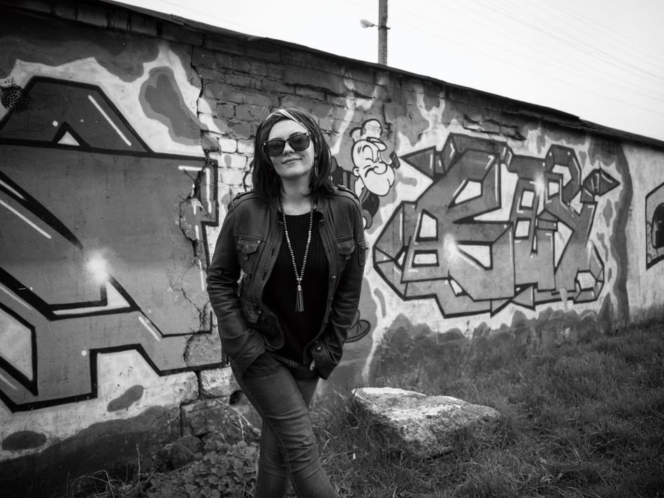 Graffiti Standing Front View Portrait Young Adult Looking At Camera Building Exterior Real People Young Women Hands In Pockets Lifestyles One Person Happiness Outdoors Smiling Leisure Activity Day Beautiful Woman Architecture People Bw Scarf Accesories Trendy Look Lifestyle