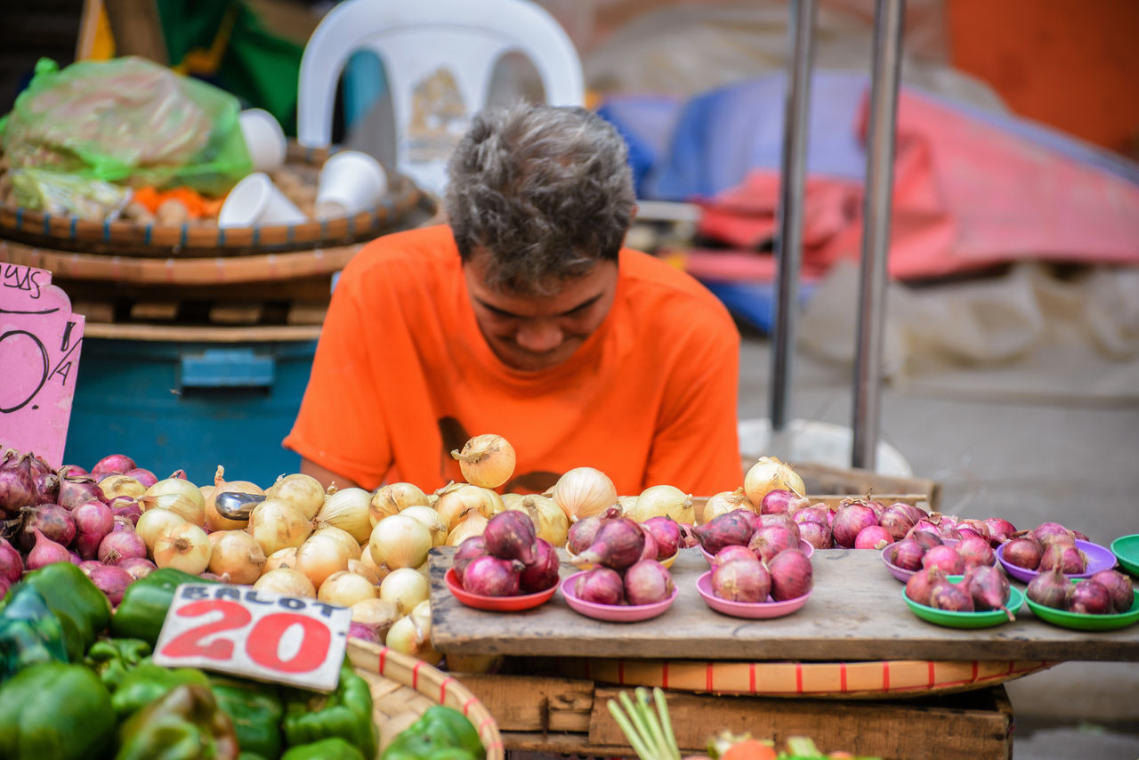 market stall, market, freshness, retail, for sale, food and drink, choice, real people, market vendor, one person, variation, food, price tag, abundance, small business, healthy eating, day, large group of objects, outdoors, men, occupation, people