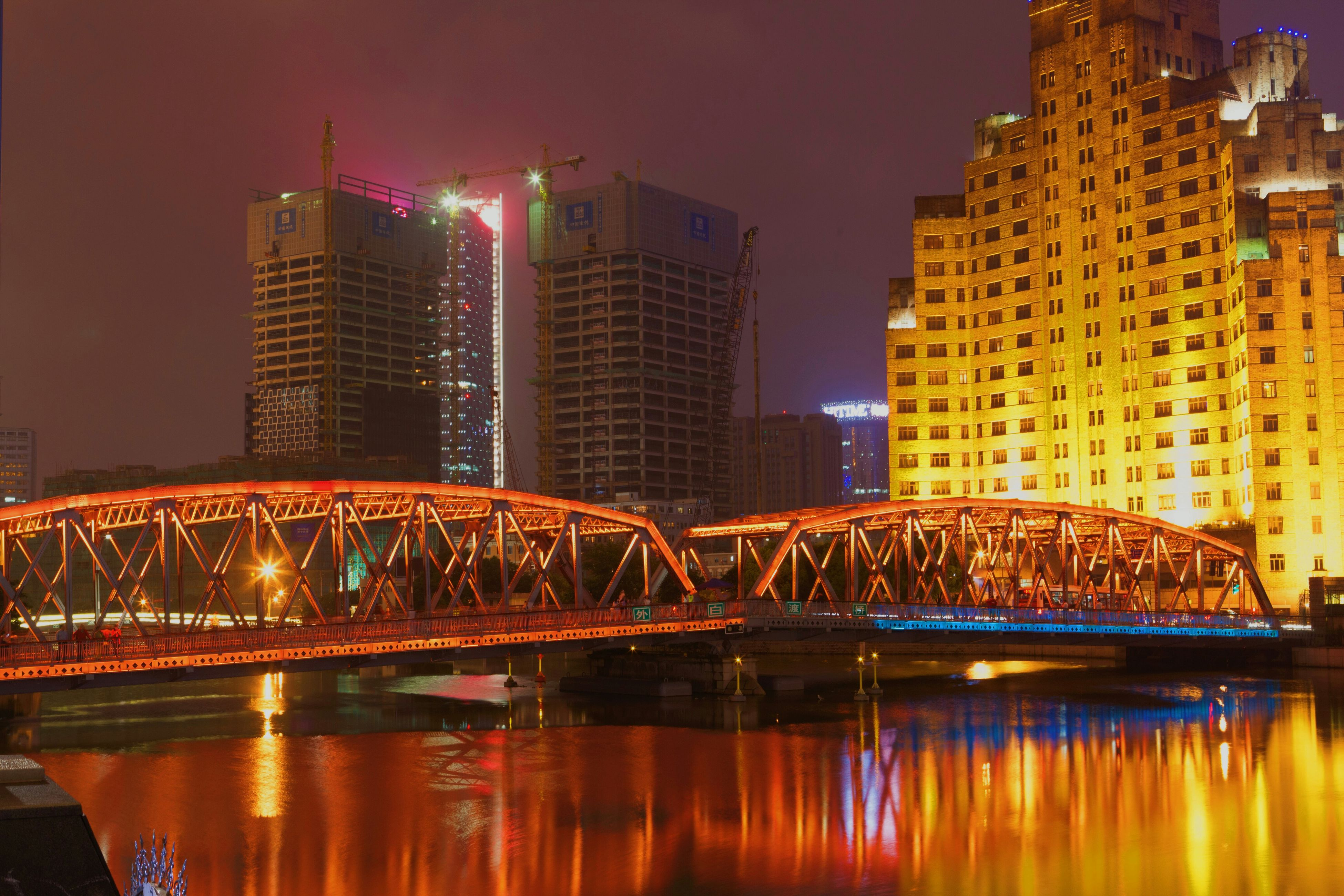 architecture, built structure, illuminated, building exterior, city, night, water, bridge - man made structure, river, connection, waterfront, capital cities, reflection, famous place, travel destinations, modern, skyscraper, cityscape, engineering, travel