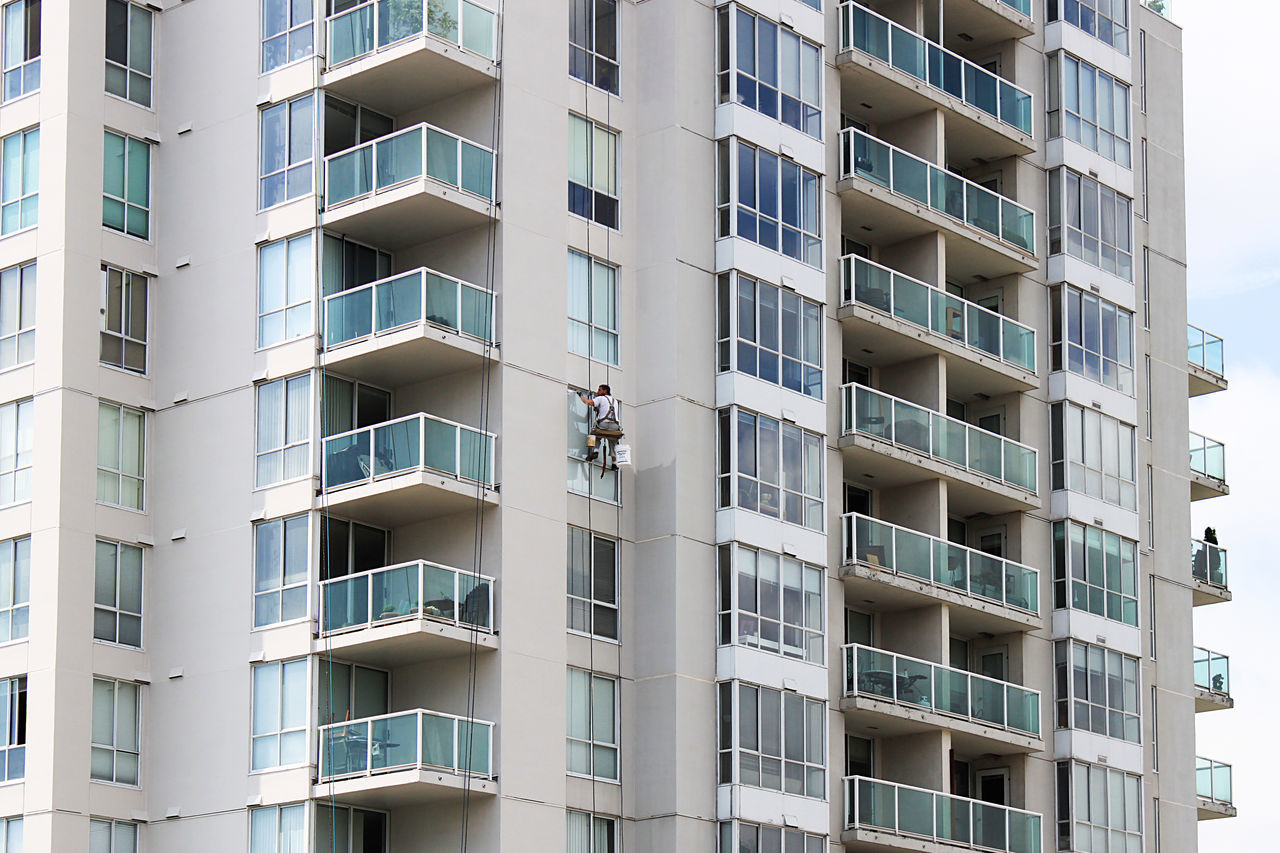 a man is working outside of a sky scaper in Vancouver, Canada Arbeit Architecture Balcony Building Built Structure City City Life Fenster Hochhaus In A Row Low Angle View Man At Work Outdoors Sky Scraper Straßenfotografie Street Photography Urban Urban Geometry Window Work
