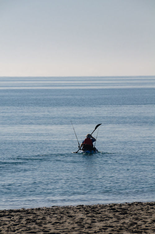 A canoeist with fishing rods paddling on the Mediterranean Sea on a beautiful sunny day with blue sky at the Costa Blanca in Spain. Beach Beauty In Nature Canoe Canoeist Fishing Hobby Horizon Over Water Kajak Mediterranean Sea Nature One Person Outdoors Rod Sea Silhouette Tranquil Scene Tranquility Vacation Water