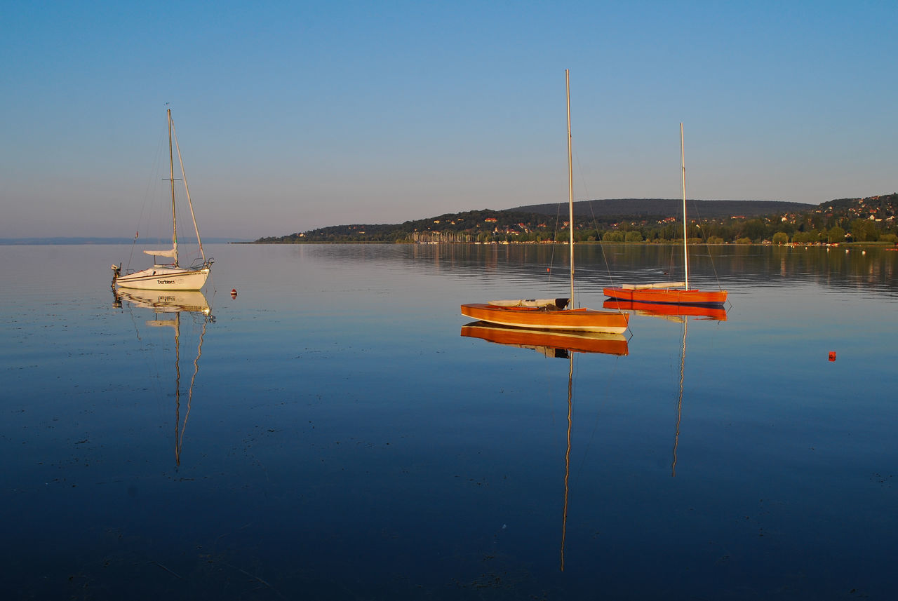 water, reflection, tranquility, nature, tranquil scene, beauty in nature, nautical vessel, lake, outdoors, transportation, scenics, no people, day, mode of transport, moored, wooden post, waterfront, sailboat, clear sky, sky