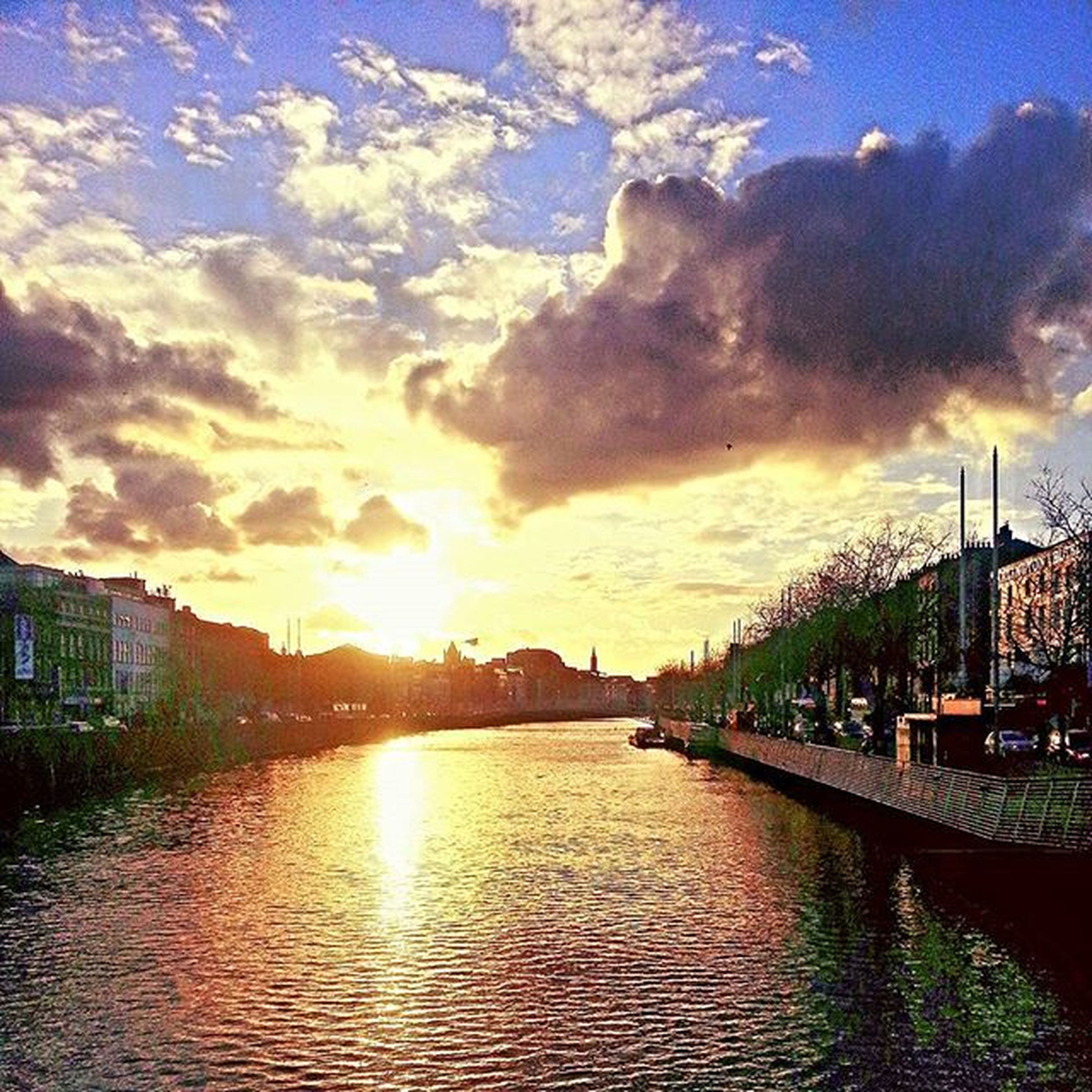 building exterior, architecture, built structure, sky, sunset, water, city, cloud - sky, river, sun, waterfront, cloud, canal, sunlight, residential building, cityscape, residential structure, building, residential district, reflection