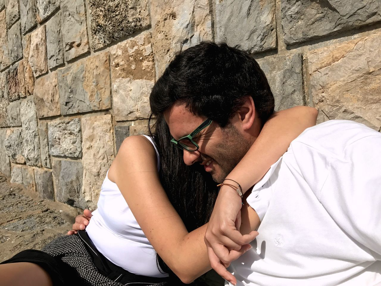 Couples Embracing While Sitting Against Stone Wall