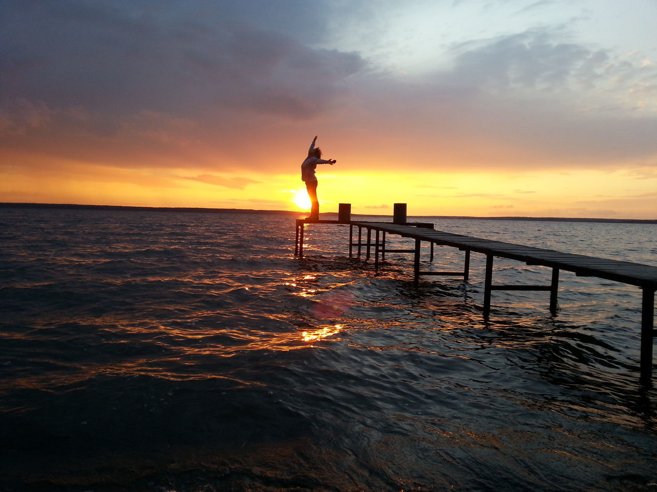 sunset, sea, water, beauty in nature, one person, silhouette, sky, nature, scenics, orange color, real people, tranquil scene, standing, cloud - sky, lifestyles, leisure activity, outdoors, horizon over water, jumping, full length, day, people